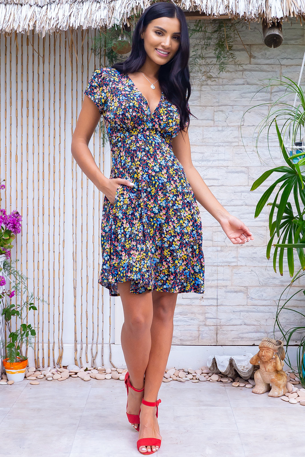 The Maggie May Ink Picnic Dress features gathered bust with basque underneath, waist features comfortable elastic shirring at back, cap sleeves, side pockets, flirty skirt draping from underneath bust and 100% rayon in ink base with small, colourful floral print.