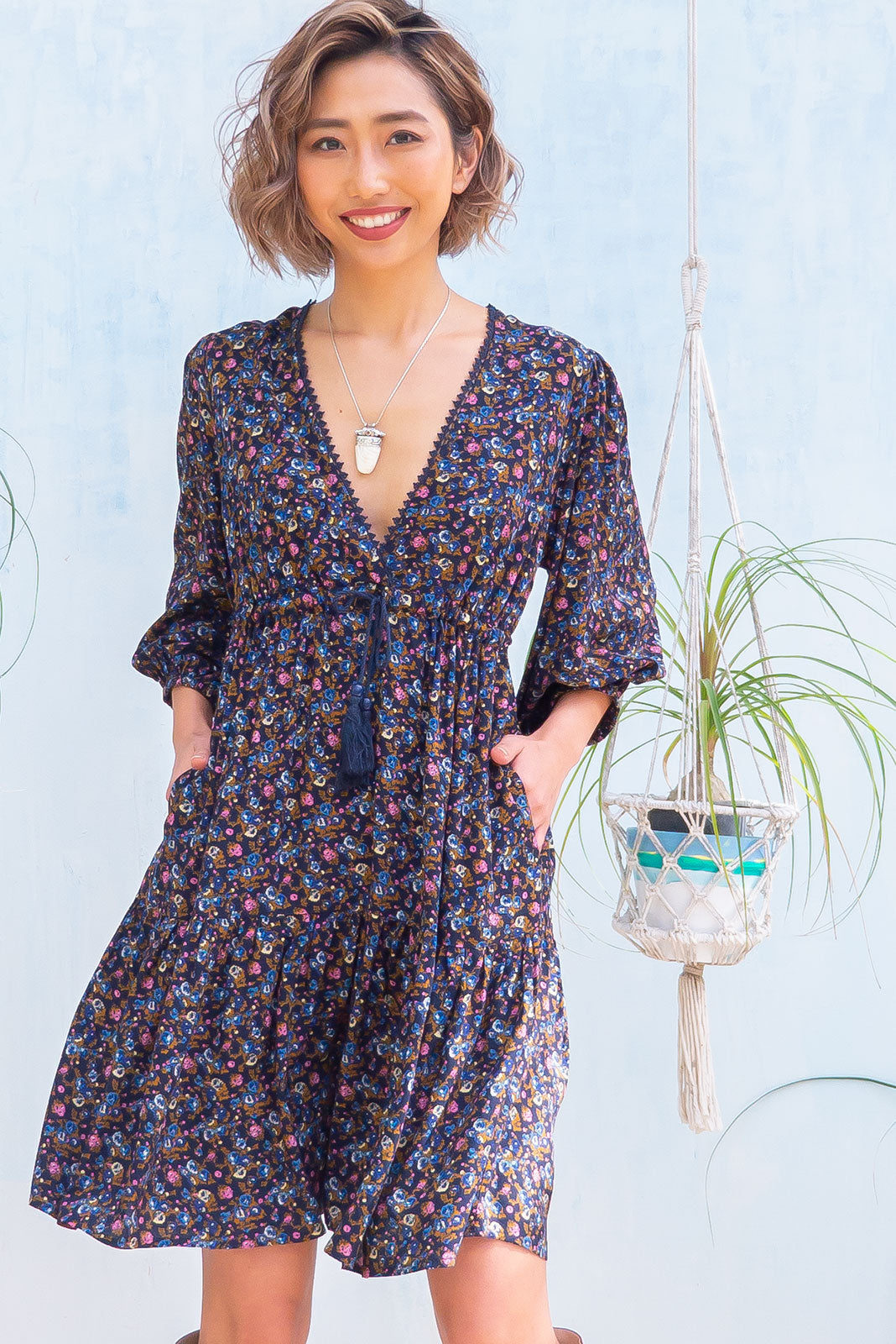 The Mariette Melody Navy Dress features deep V neckline with lace detail, puff long sleeves, side pockets, adjustable drawstring waist and woven 100% rayon in navy base with sweet blue floral print.
