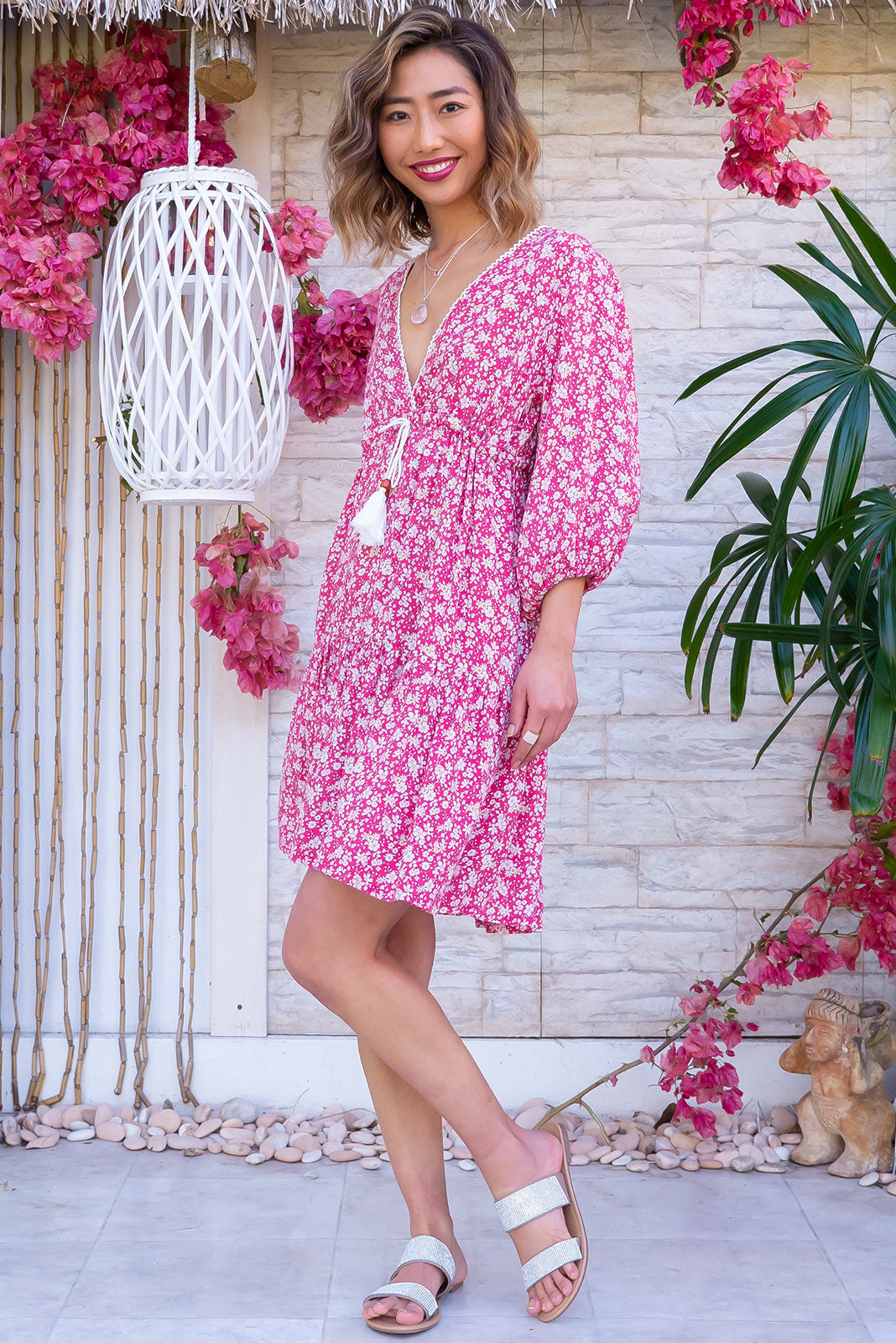 The Mariette Strawberry Rambles Dress Features deep V neckline with lace detail, puff sleeves, side pockets, adjustable drawstring waist and 100% rayon in pastel strawberry red base with white and yellow floral print.