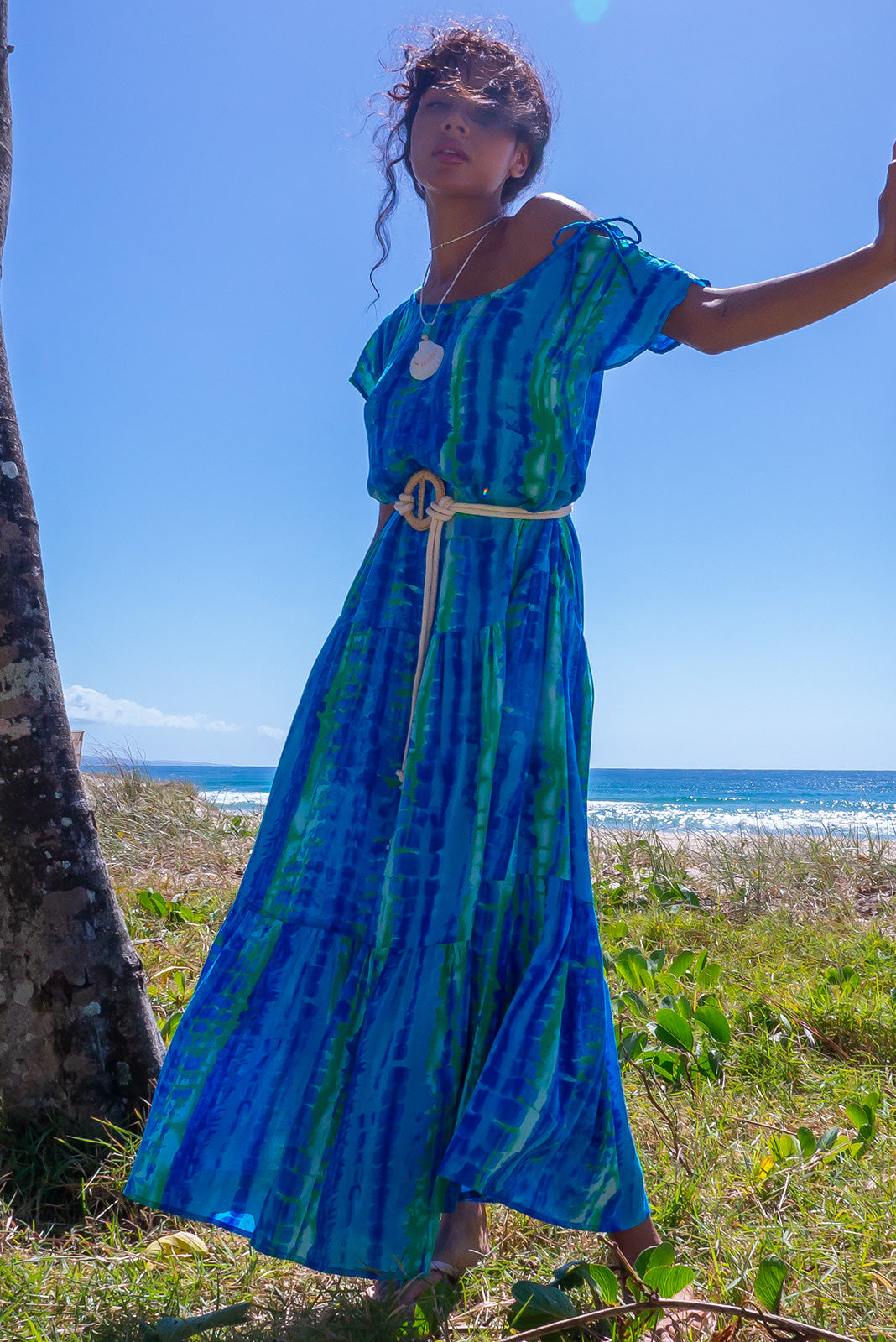 The Marina Bolo Blue Maxi Dress can be worn off shoulder and features adjustable side neck tie, drop waist with tiered skirt, side pockets, rope belt included and 100% rayon in blue and green tie dye print, print placement may vary.