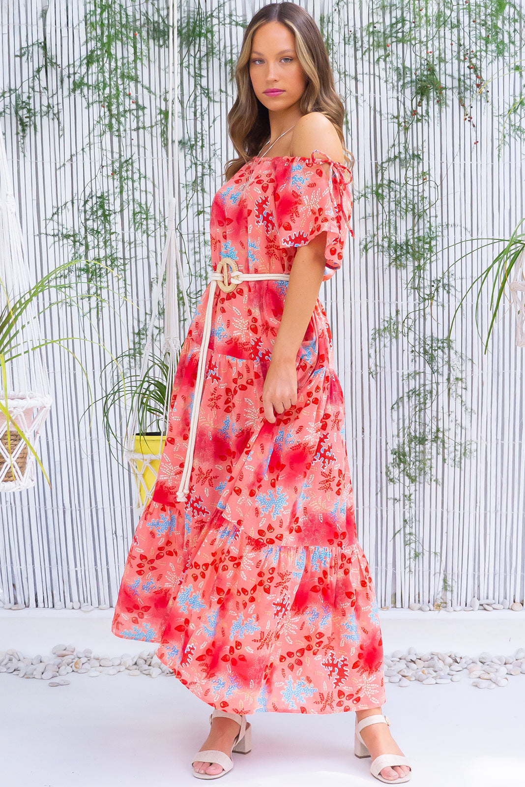 The Marina Coral Cay Maxi Dress features adjustable side neck tie, drop waist with tiered skirt, side pockets, rope belt included and cotton, viscose blended fabric in coral wash effect print.
