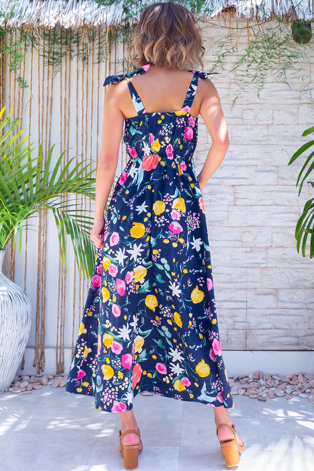 The Midsummer Emilia's garden Dress features straight neckline, tie up shoulder straps, functional shell button front, side pockets, elasticated waist back and woven 100% cotton poplin in navy base with bright, retro floral print.