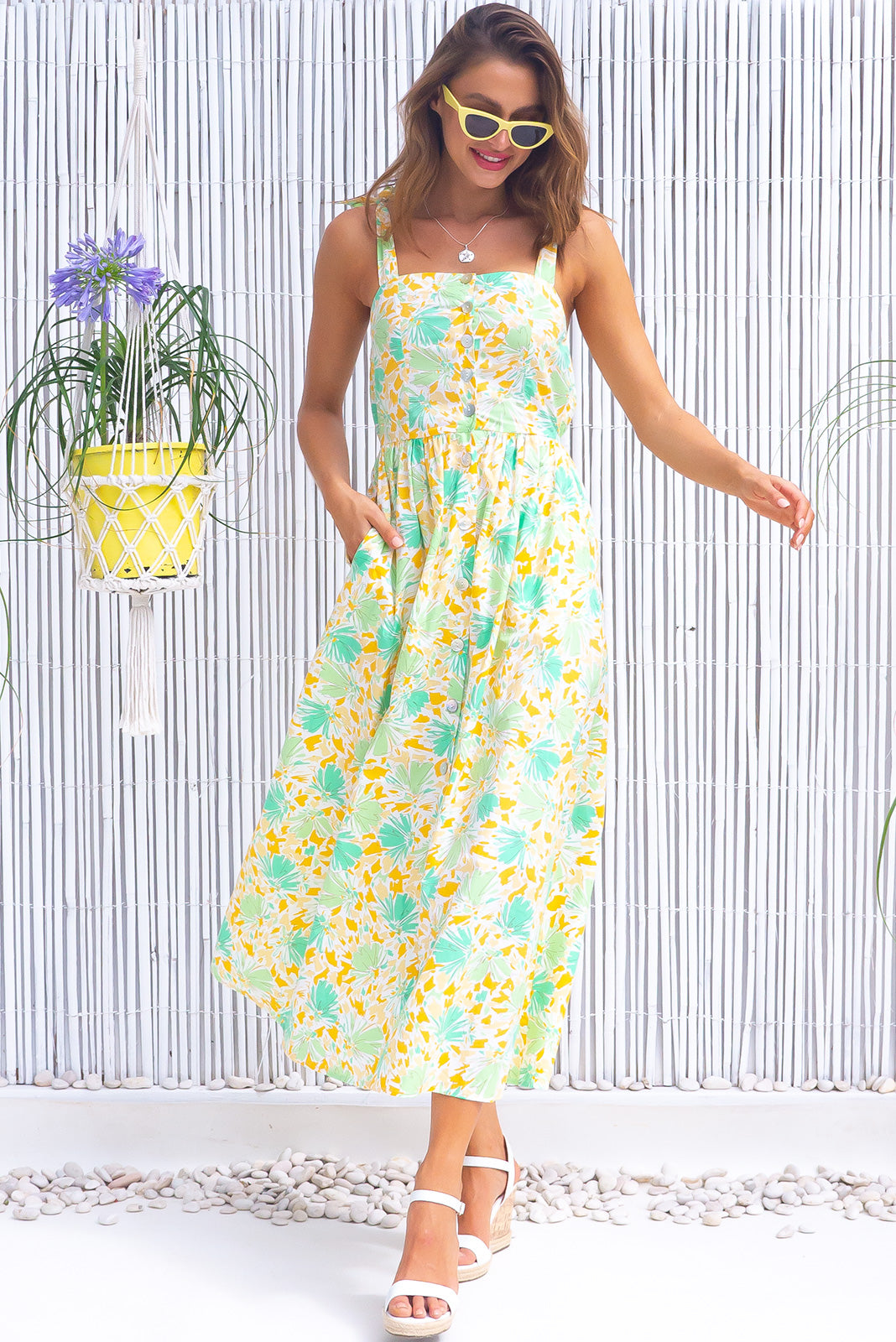The Midsummer Lemon and Lime Dress features straight neckline, tie up shoulder straps, functional shell button front, side pockets, elasticated waist back and woven 100% cotton poplin in white base splashed with a bright, yellow and green print.