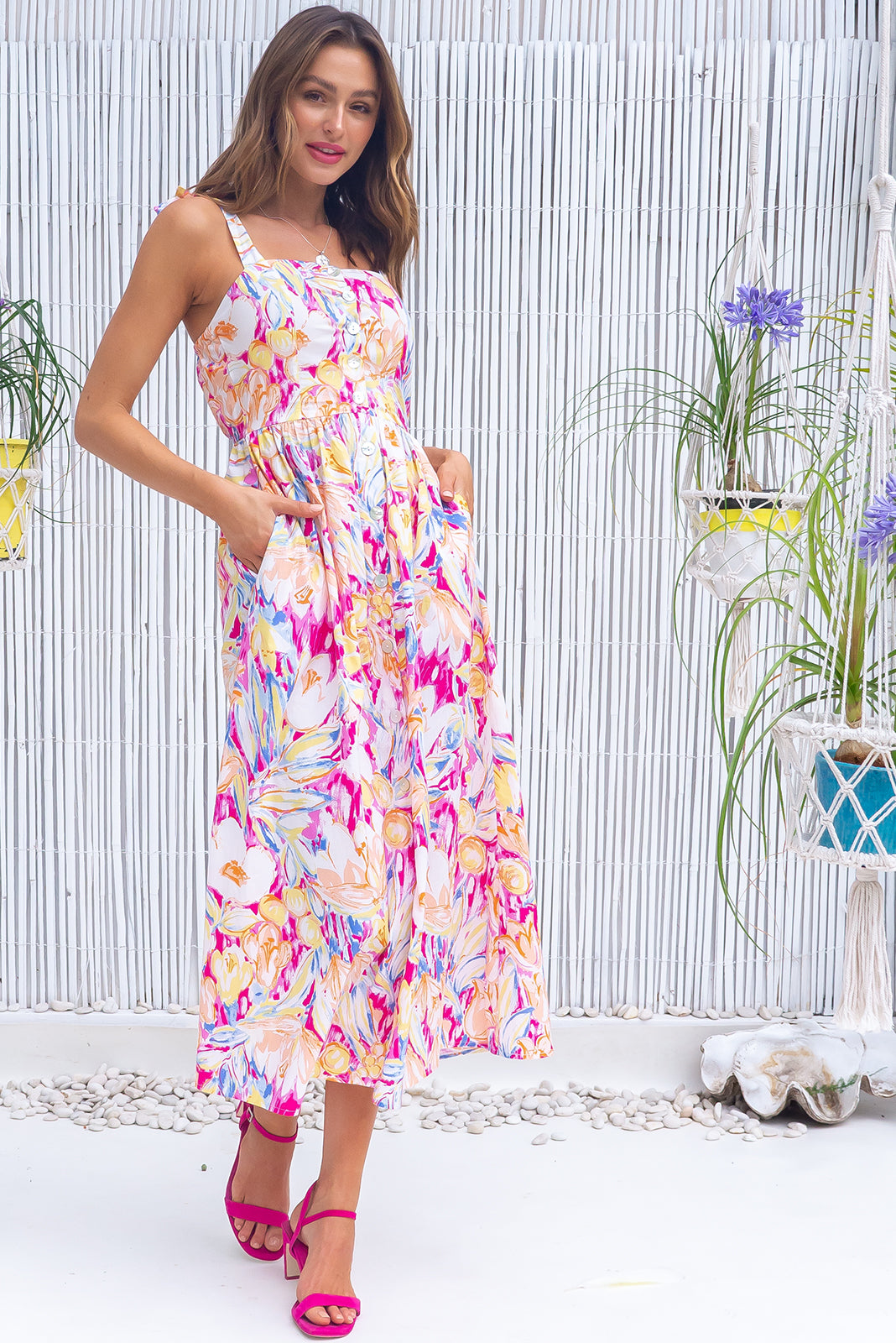 The Midsummer Monet Pink Dress features straight neckline, tie up shoulder straps, functional shell button front, side pockets, elasticated waist back and woven 100% cotton poplin in pink, orange, yellow, white and lilac abstract floral print.