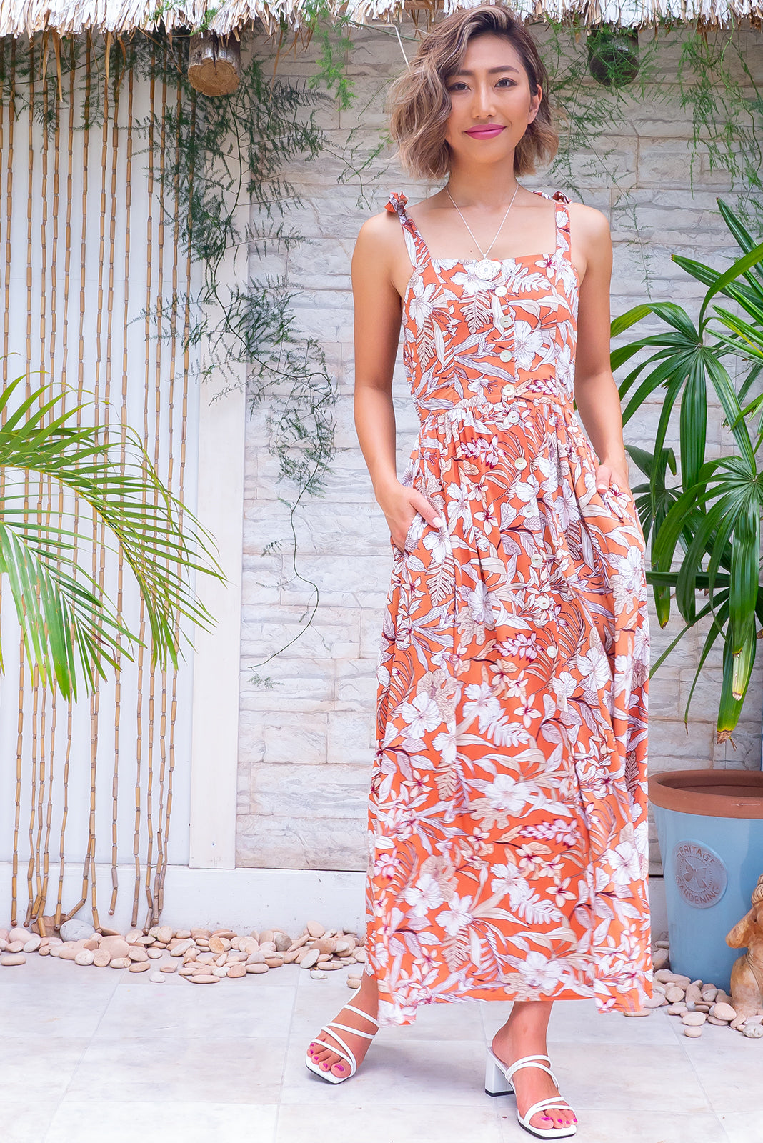 The Midsummer Terracotta Siesta Dress features straight neckline, tie up shoulder straps, side pockets, elasticated waist back and 100% viscose in terracotta base with beige and cream tropical print.