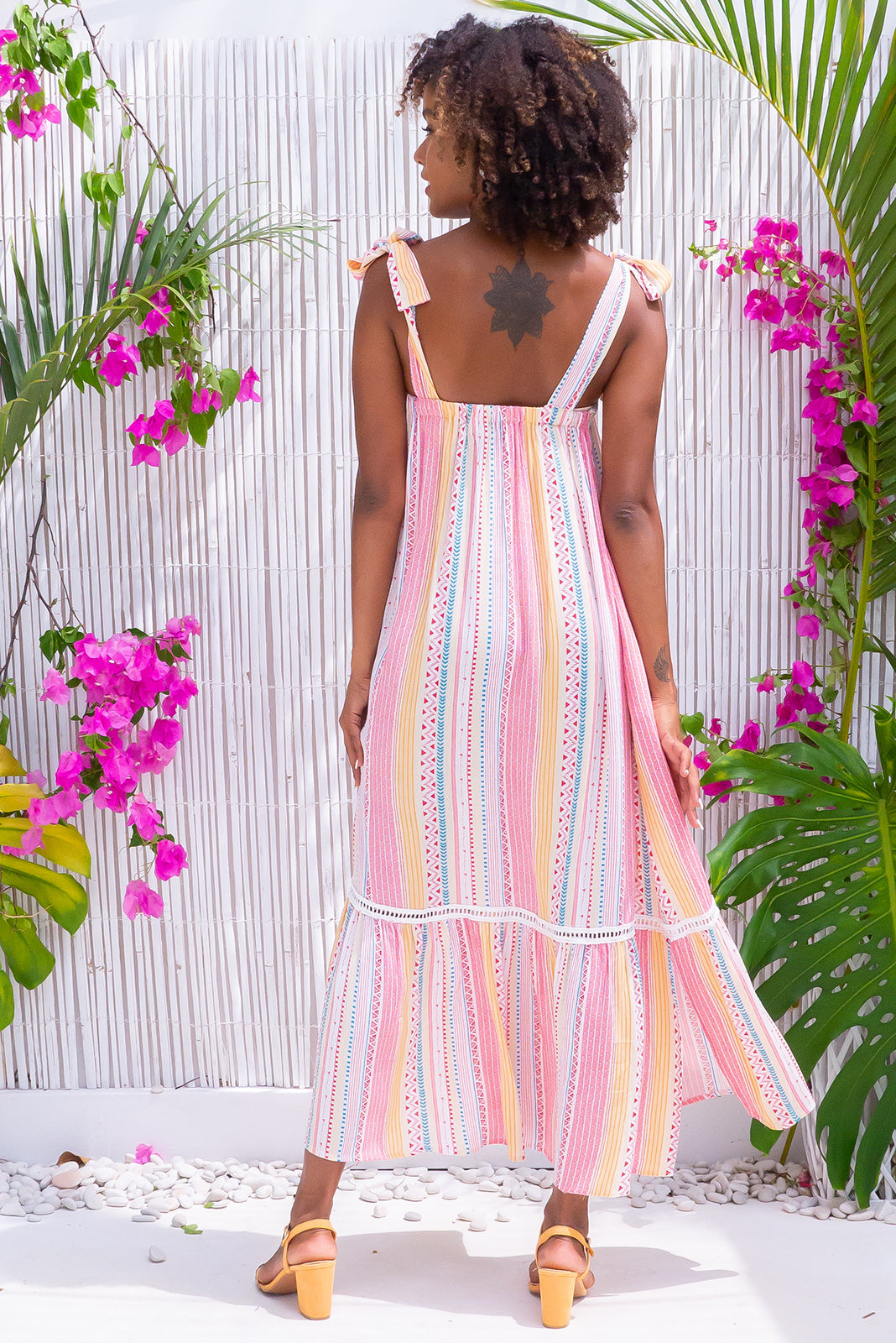 Moon Kiss Lucky Stripes Maxi Dress made in woven 100% crinkle viscose in vertical stripes and shapes in white, blue, pastel yellow, gold and watermelon tones features adjustable tie up straps, lace detailing around top, small split detail on both sides of hem, side pockets, frill hem feature.