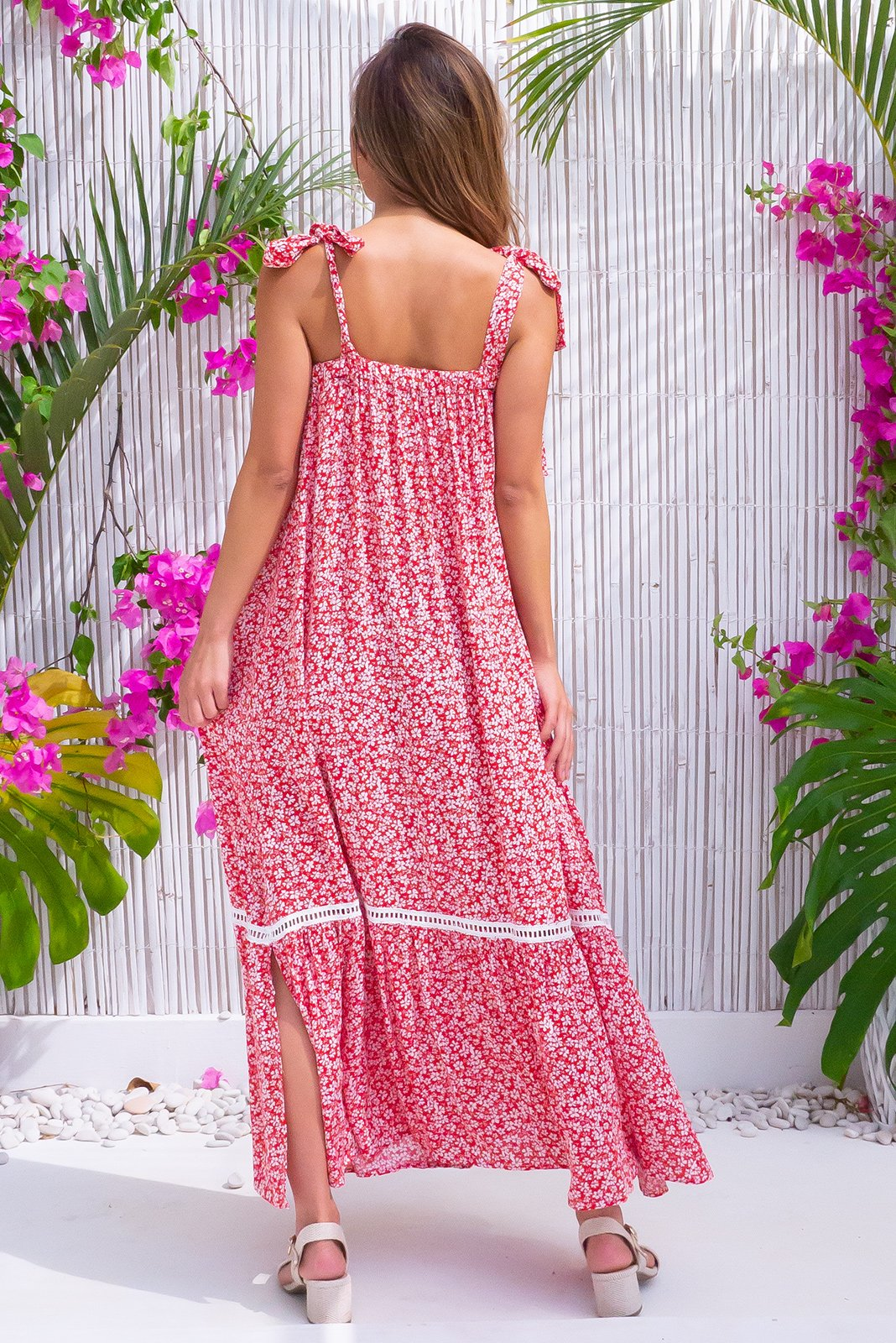 The Moon Kiss Red Daisy Maxi Dress is a fun and vintage inspired frock featuring adjustable tie up straps, lace detail around top, side pockets, lace insert above frill hem feature, small split detail on both sides of hem in bright red base with white daisy print in woven 100% crinkle texture viscose.