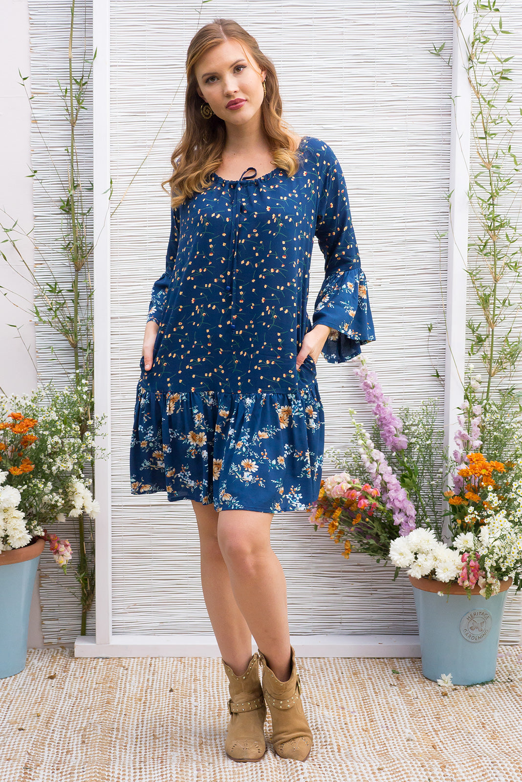 Moon River Navy Dress features a drop waist and 3/4 sleeves with a boho frill and a cord drawstring neck in a intricate boho mix and match vintage print in tonal blue shades on a soft woven rayon