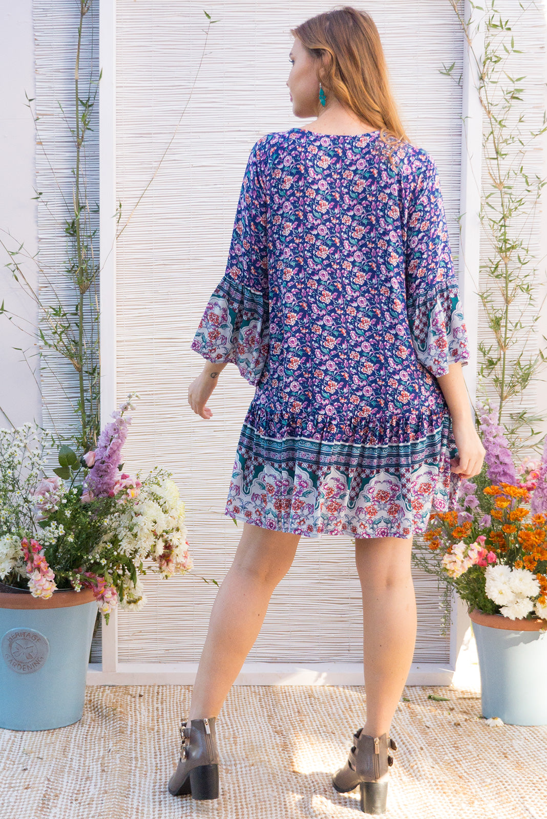 Moon Slice Navy Bliss Dress features a drop waist and 3/4 sleeves with a boho frill and a cord drawstring neck in a intricate boho border print in jewel tones on a soft woven rayon