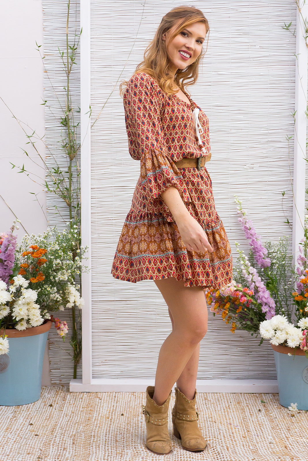 Moon Slice Dress in Rust Red Desert Print features a drop waist and 3/4 sleeves with a boho frill and a cord drawstring neck
