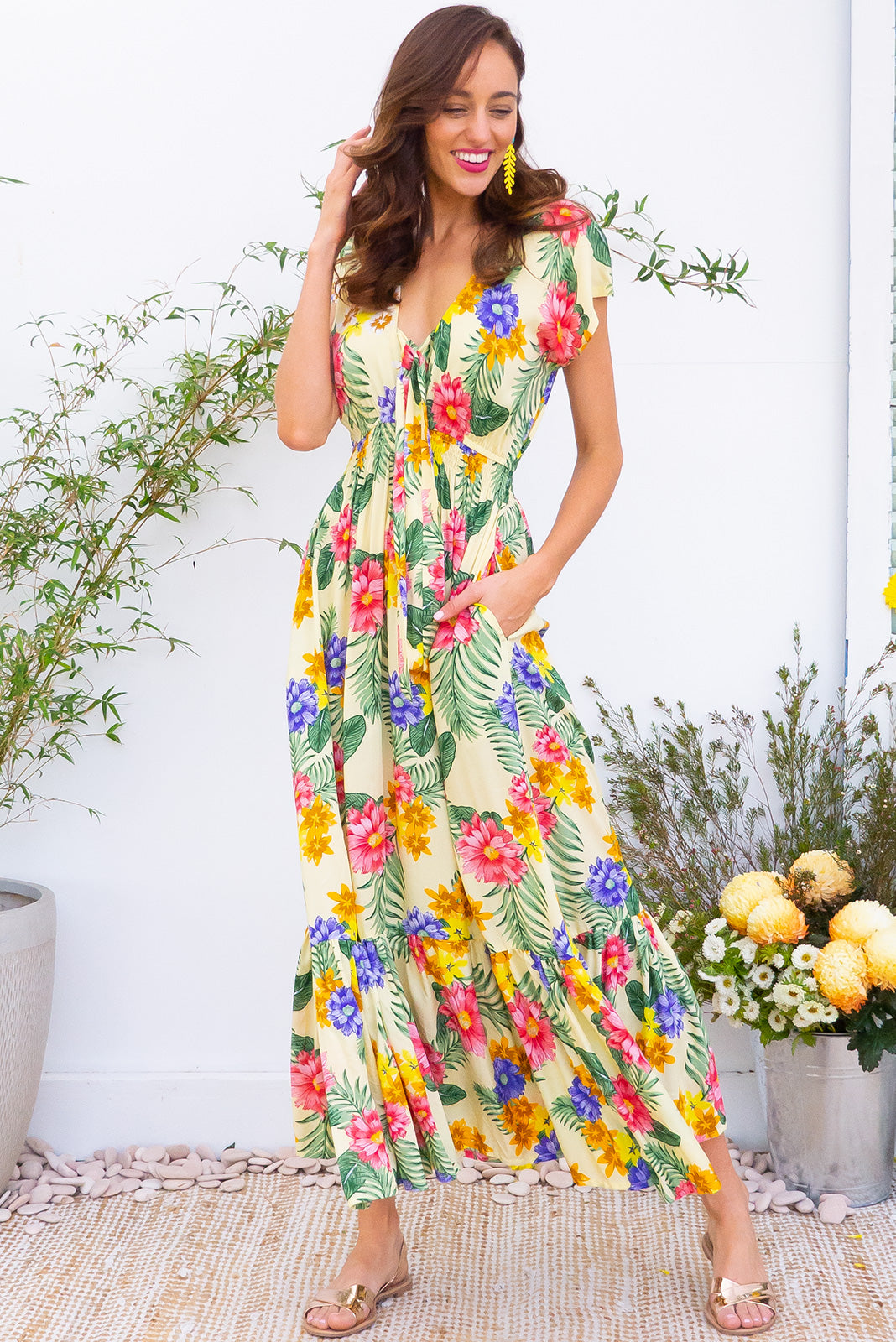Nellie Tropical Sunshine Maxi Dress Maxi dress features elasticated empire line with a cap sleeve and deep v neck the fabric is a soft woven rayon in a soft yellow based tropical inspired floral print