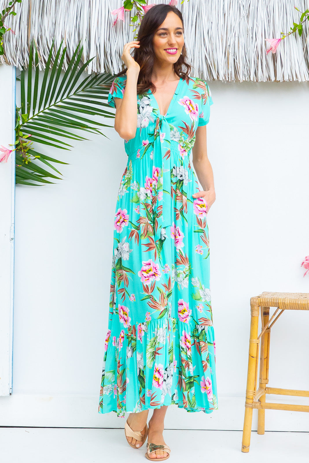 Nellie Tropical Turquoise Maxi Dress Maxi dress features elasticated empire line with a cap sleeve and deep v neck the fabric is a soft woven rayon in a soft mint green based tropical inspired floral print