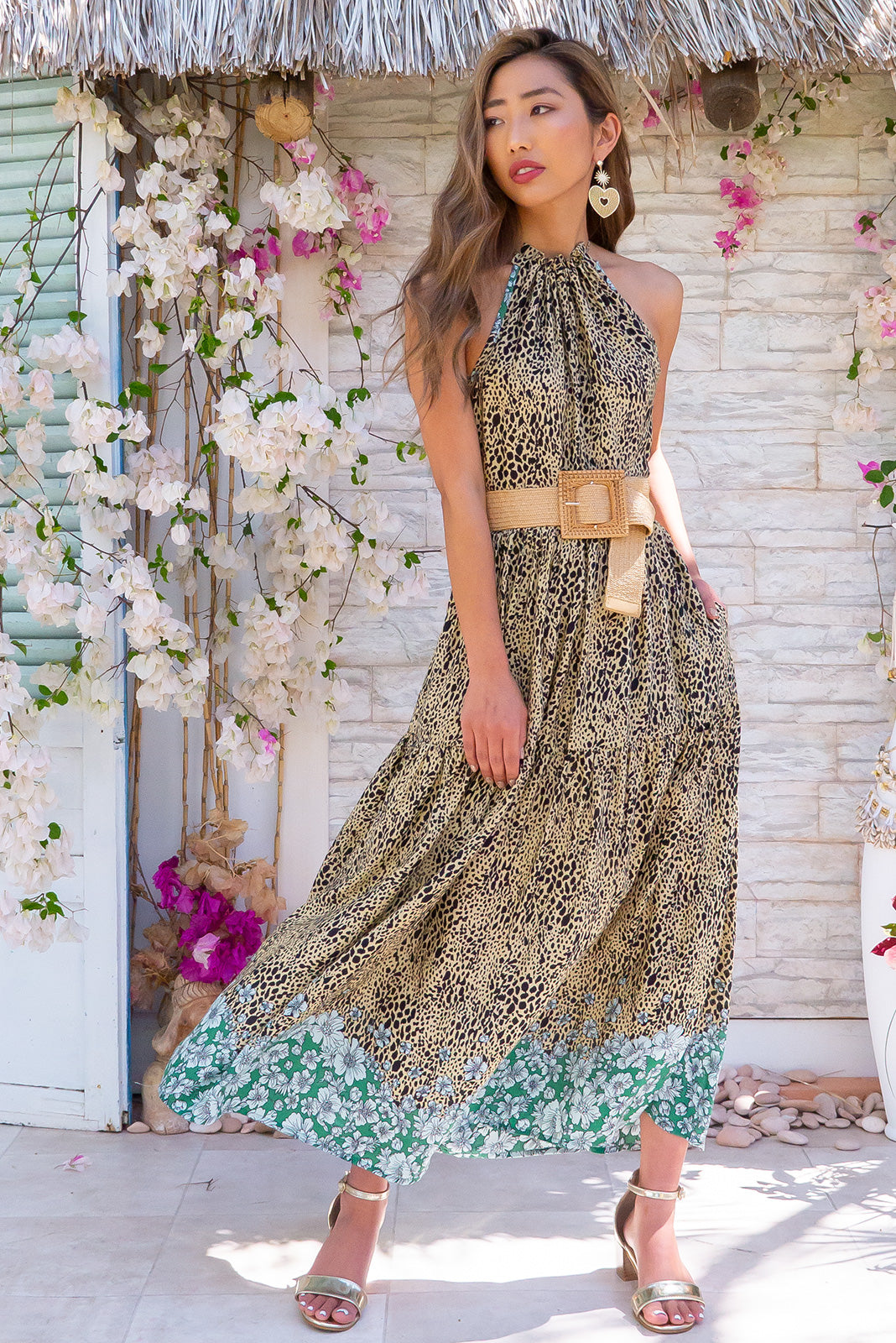 Noosa Nala Maxi Dress Leopard Print Bohemian inspired, features complimentary rattan belt, halter neck, adjustable string neckline, side pockets, tiered skirt and woven 100% rayon in a beige base covered with black animal spots with contrasting green floral border print.