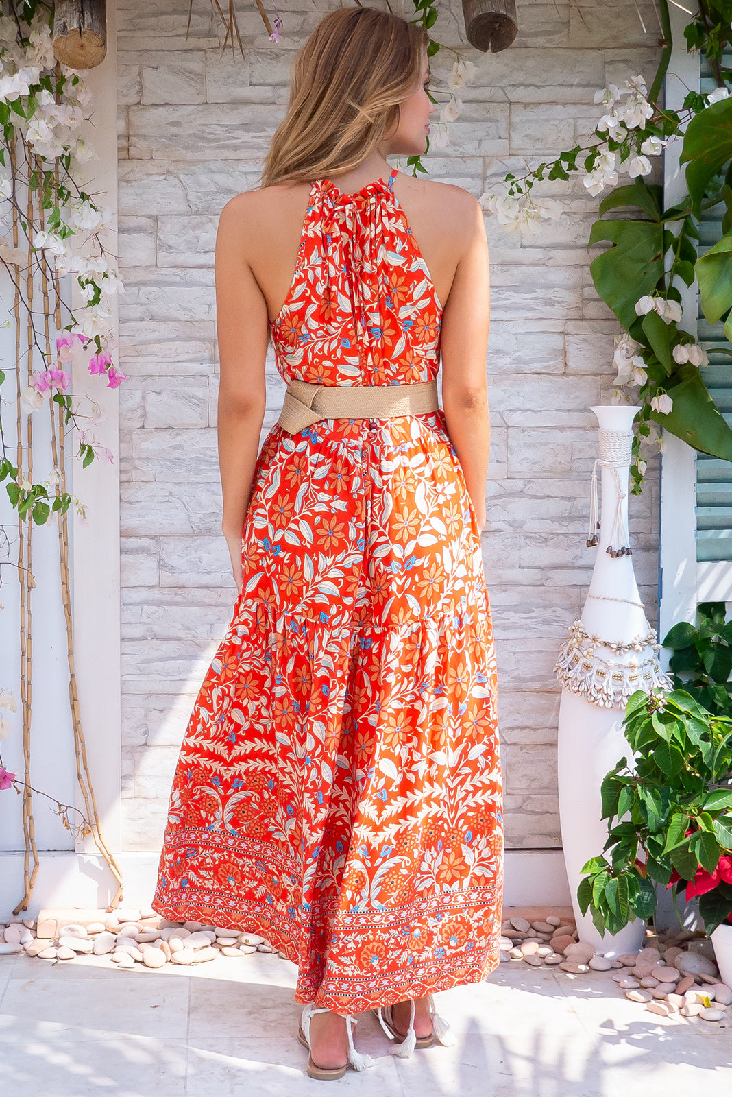 Noosa Red Gems Maxi Dress, bohemian summers style, 100% rayon, halter neck, adjustable string neckline, tiered skirt, side pockets, bright red base with large multicoloured floral print featuring white, peach and blue, bohemian-style rattan waist belt included.