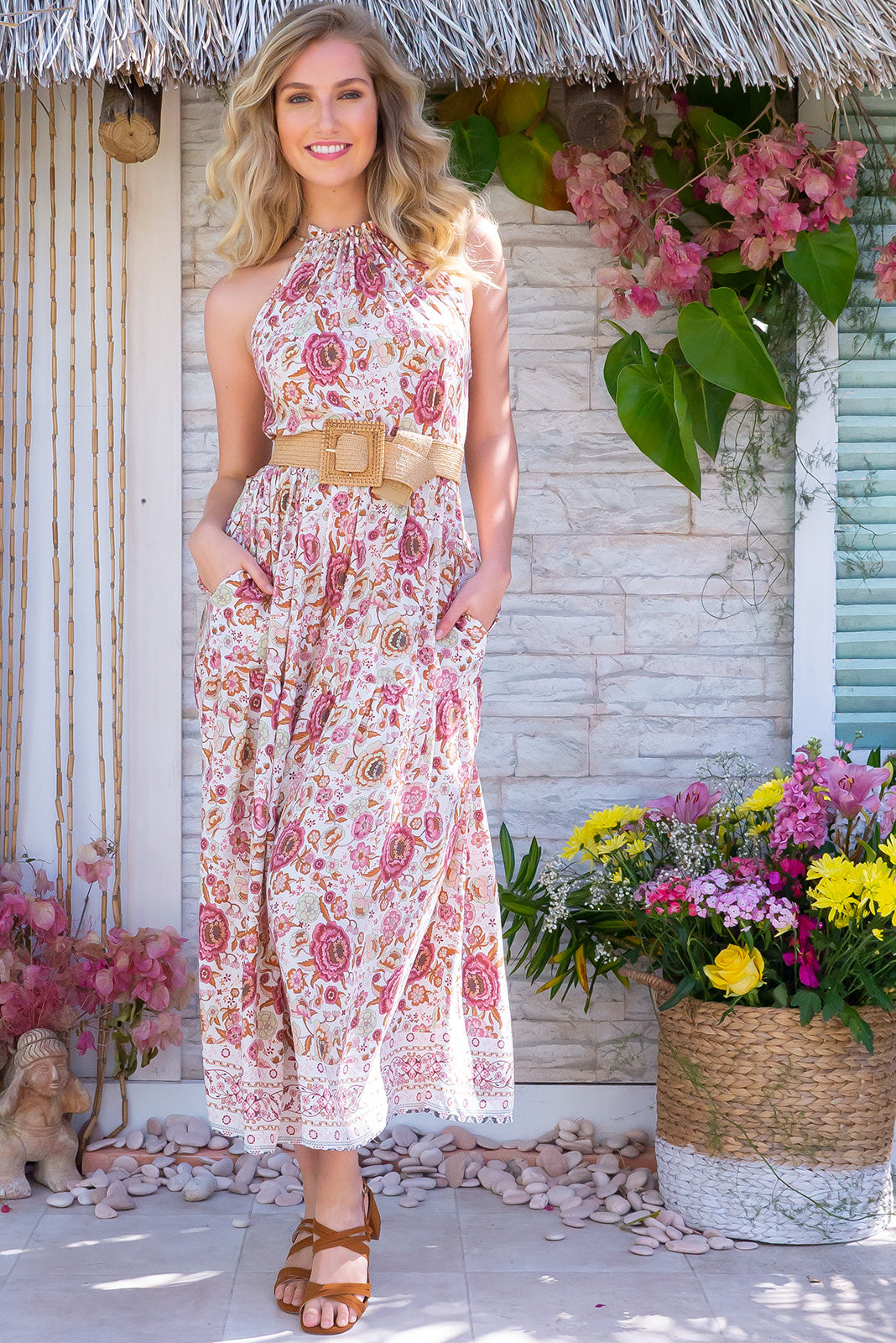Noosa Tea Rose Maxi Dress features a high neck halter design with adjustable ties, a bohemian pink print, side pockets, tiered skirt, complimentary belt, border print and made in 100% rayon.
