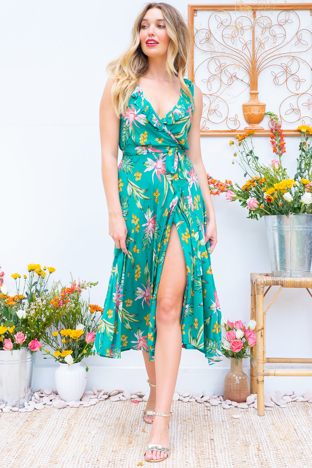 Pablo Daintree Midi Wrap Dress features a flattering wrap around shape, sleeveless bodice with a frill and comes in a strong green with a tropical inspired floral print on 100% rayon