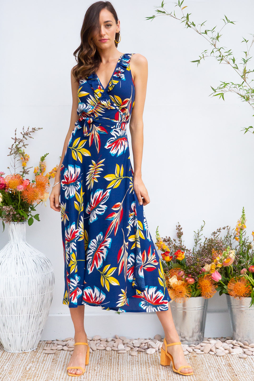 Pablo Inky Leaves Midi Wrap Dress features a flattering wrap around shape, sleeveless bodice with a frill and comes in a bright navy based tropical leaf print on rayon woven fabric
