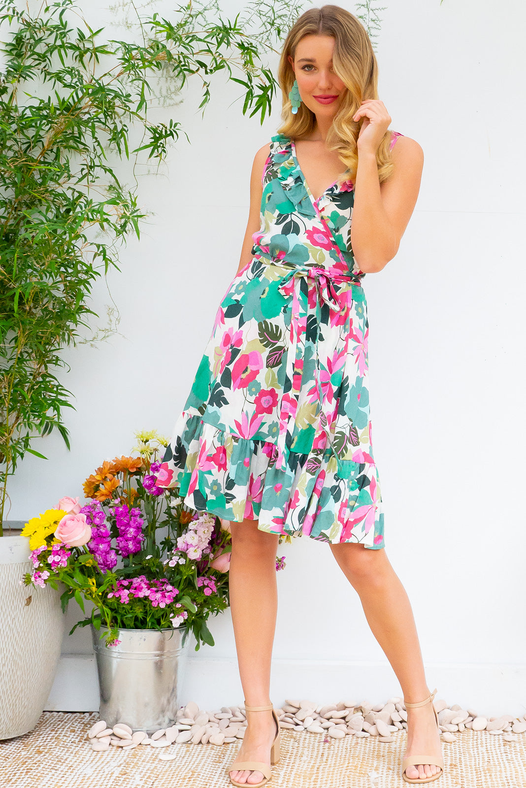 Paloma Bold and Beautiful Garden Wrap Dress features a flattering wrap around shape, sleeveless bodice with a frill and comes in a pink and green hued graphic floral print a cotton rayon blend