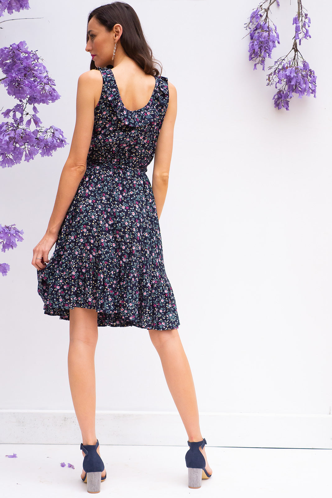 Paloma Navy Ditzy Wrap Dress features a flattering wrap around shape, sleeveless bodice with a frill and comes in a dark navy small floral print woven rayon