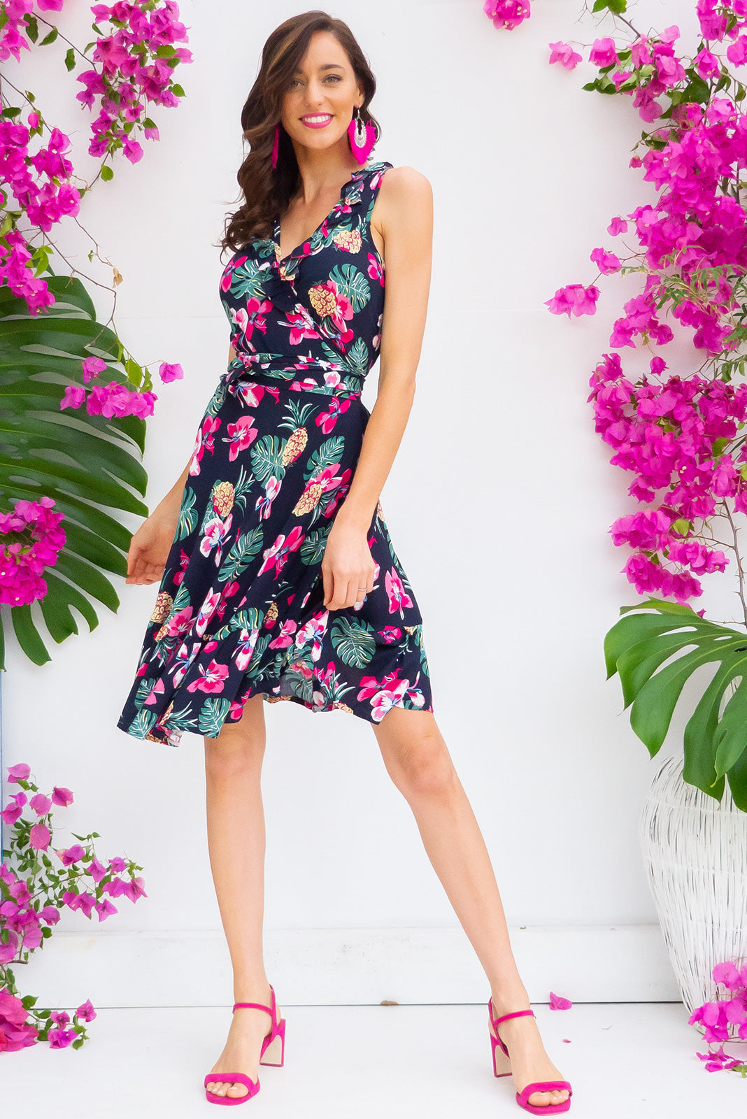 Paloma Navy Pineapple Wrap Dress features a flattering wrap around shape, sleeveless bodice with a frill and comes in a dark navy pineapple and tropical flower print woven rayon