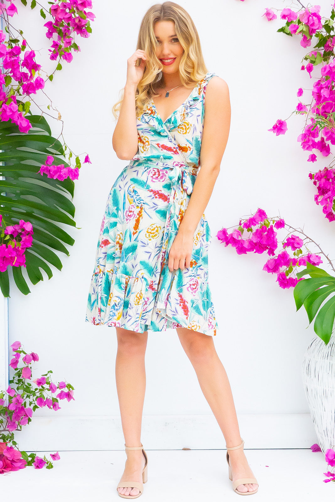 Paloma Porcelain Parrot Wrap Dress features a flattering wrap around shape, sleeveless bodice with a frill and comes in soft cream based bird and botanical print woven rayon