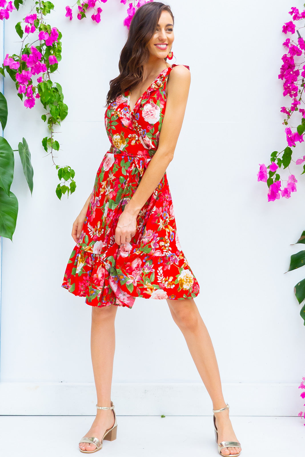 Paloma Red Roses Wrap Dress features a flattering wrap around shape, sleeveless bodice with a frill and comes in bright red floral print