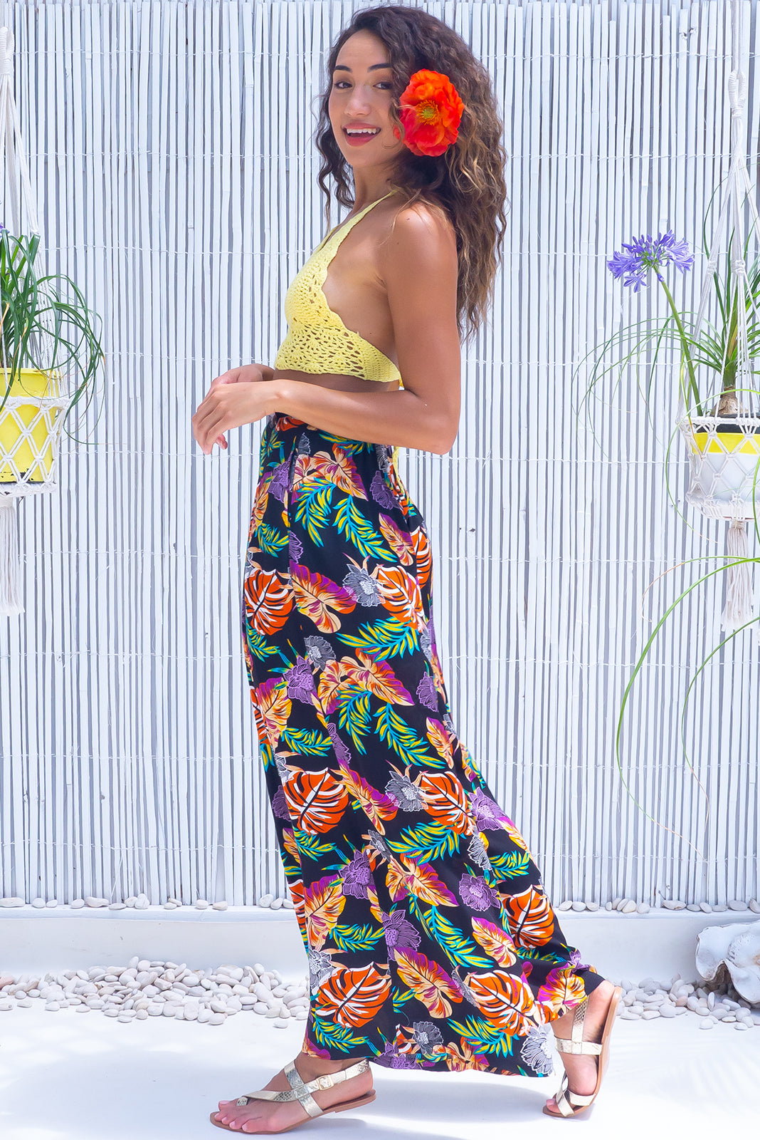 The Parakeet Jungle Flowers Pants features elasticated back of waist, belt loops with coconut button detail, side pockets and 100% viscose in black base with vibrant jungle leaf print,