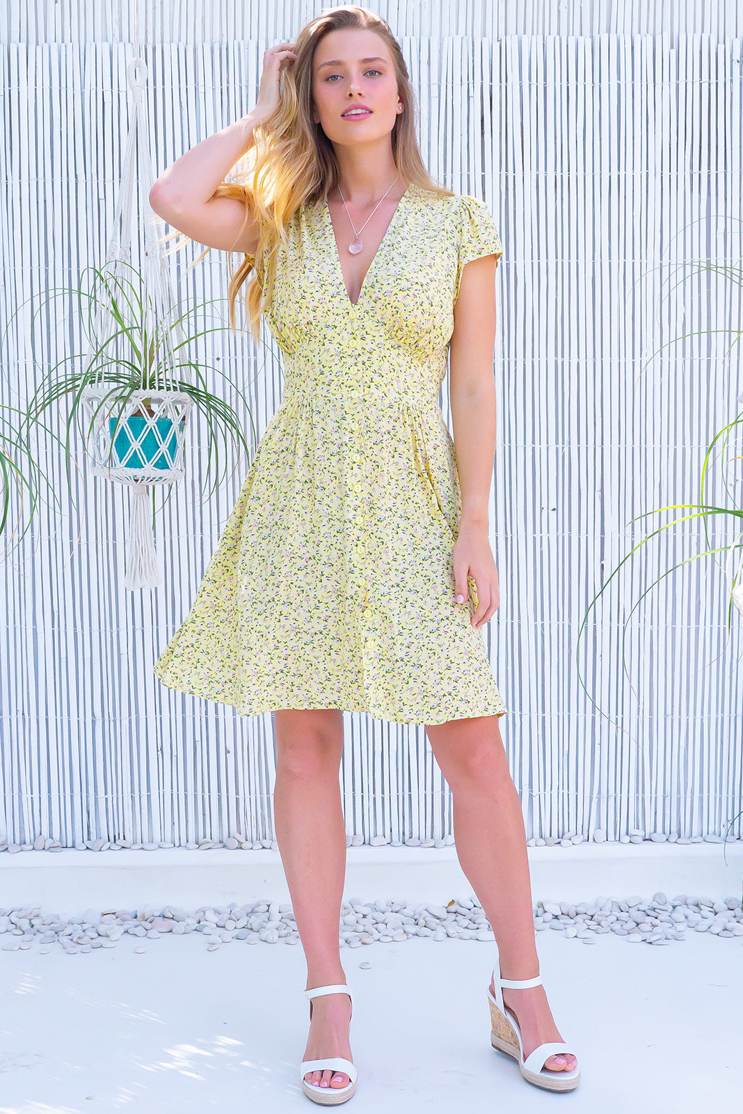 The Peggy Canary Yellow Dress features functional button front, cap sleeves, softly fitted basque waist, side pocket and 100% viscose in yellow base with ditzy floral print.