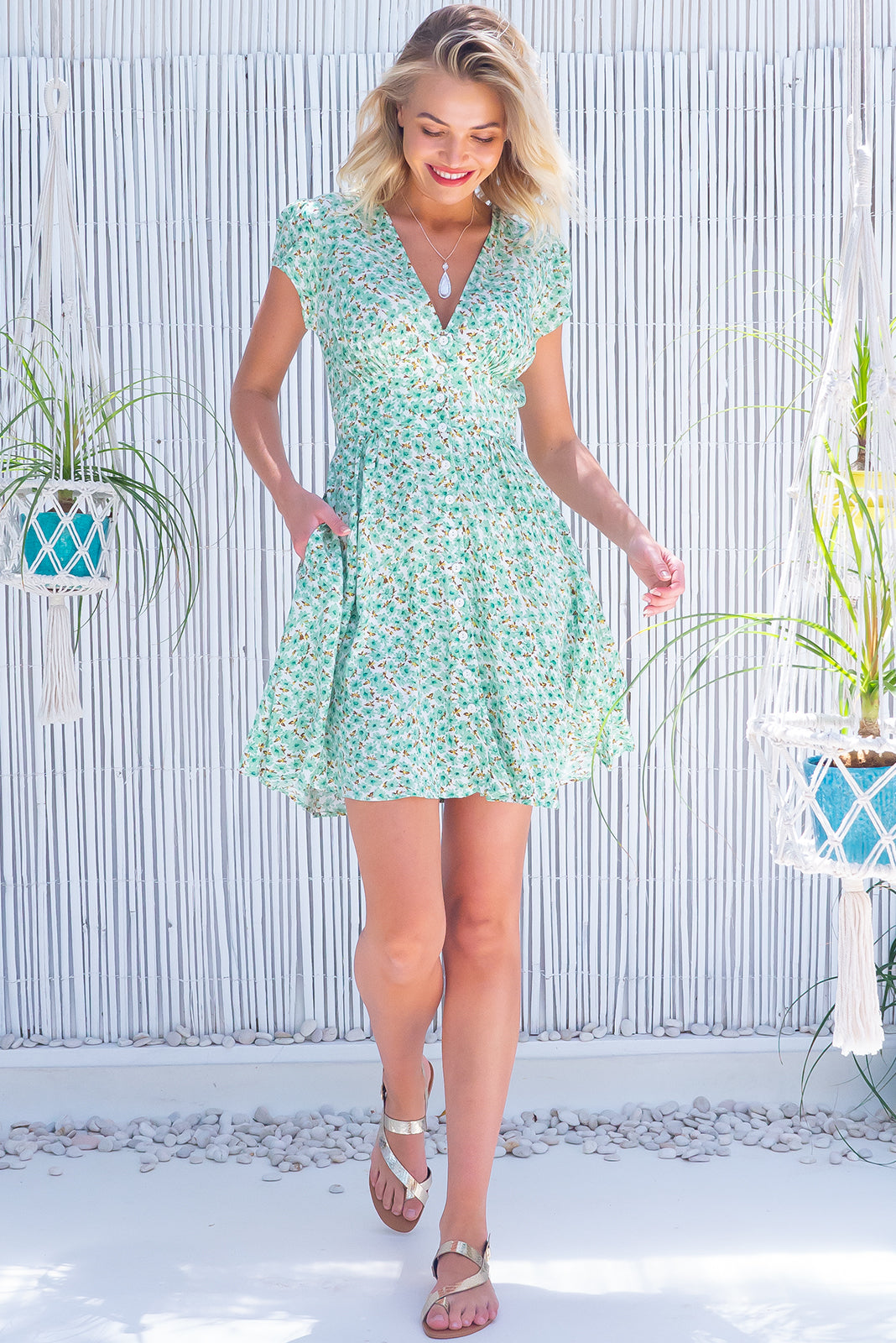 The Peggy Mint Daisy Dress features functional button front, cap sleeves, softly fitted basque waist, shirring across the back waist, side pockets and 100% viscose in white base with mint floral print.