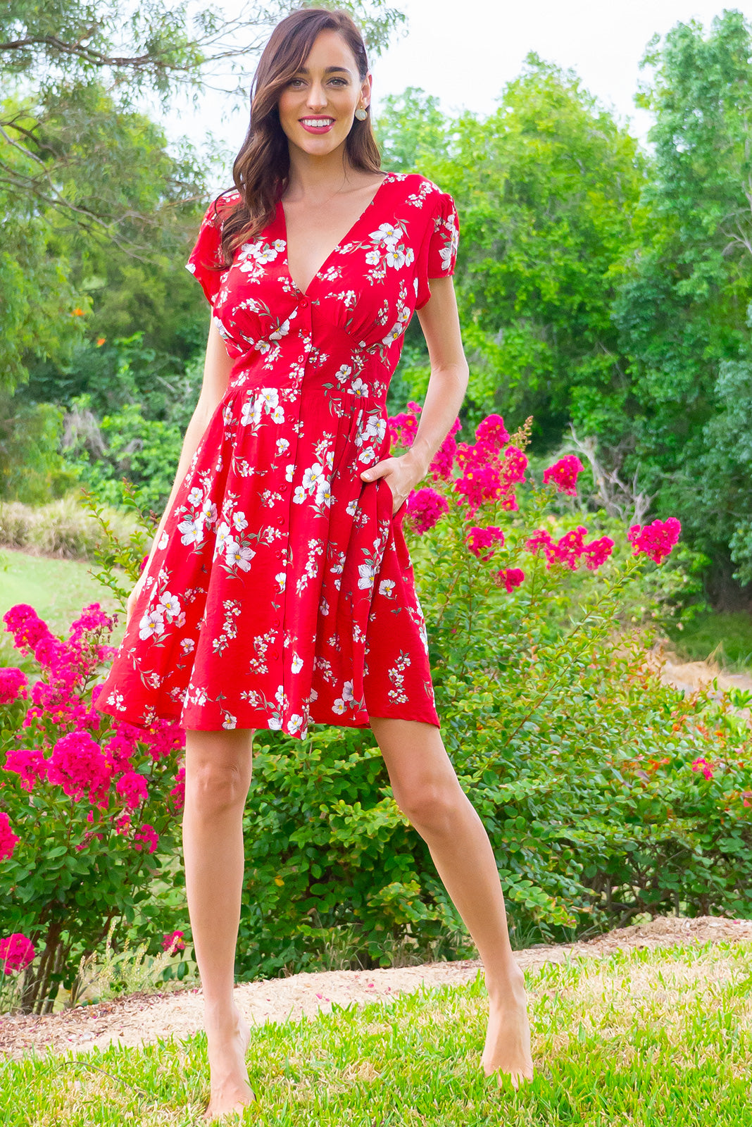 Peggy Aria Red Mini dress features a vintage inspired fitted basque waist and elasticated waist with a cap sleeve, deep v neck and a functional button front the fabric is a soft woven rayon nylon blend in a bright red floral print