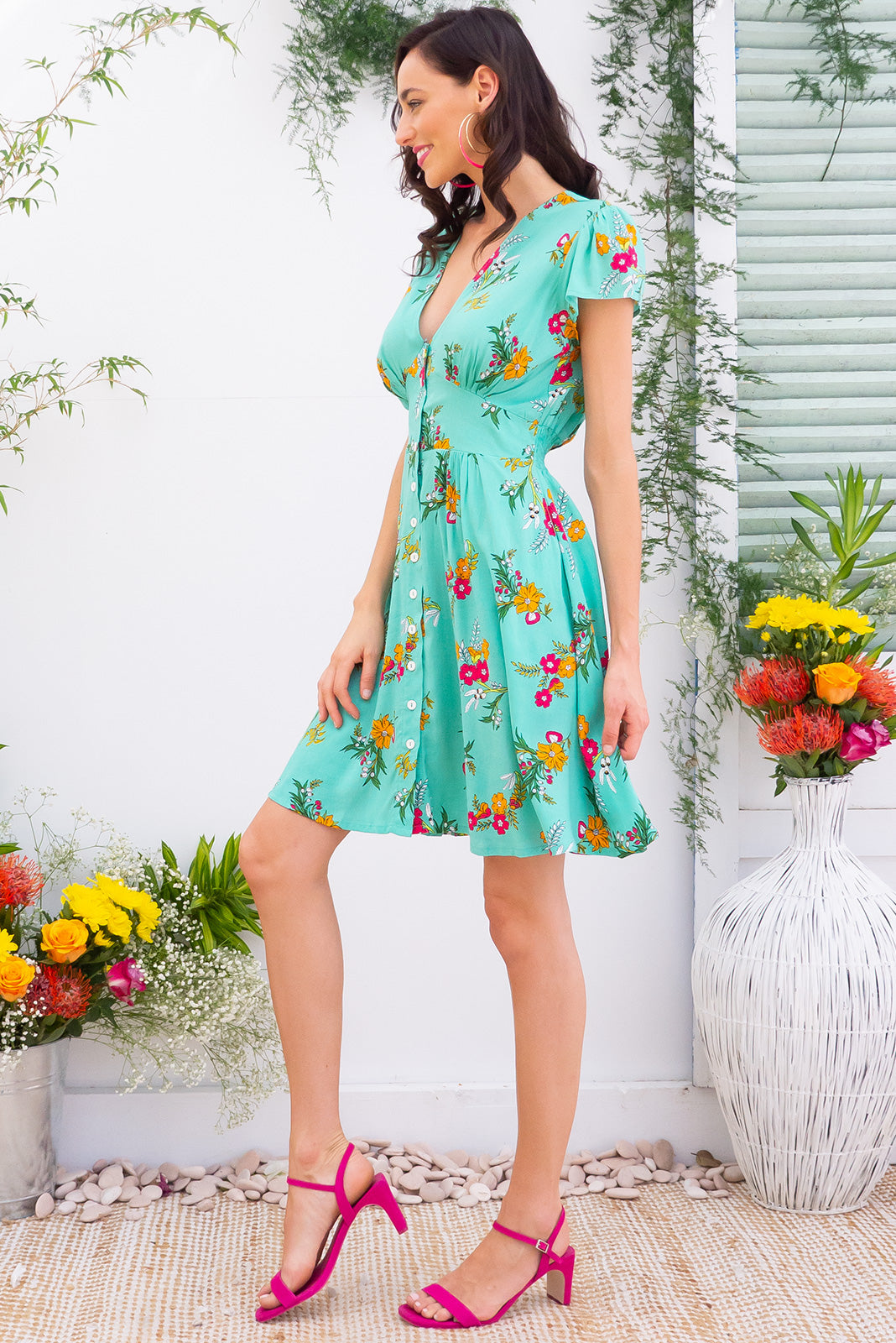 Peggy Minty Green Mini dress features a vintage inspired fitted basque waist and elasticated waist with a cap sleeve, deep v neck and a functional button front the fabric is a soft woven rayon in a fresh minty green with a bright floral print