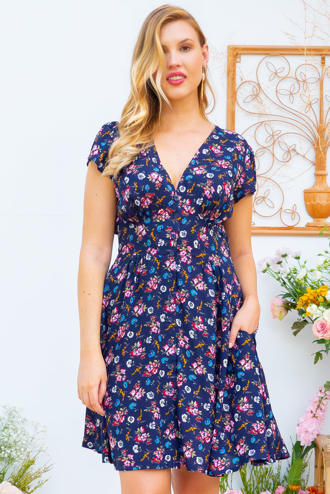 Peggy Nova Navy Mini dress features a vintage inspired fitted basque waist and elasticated waist with a cap sleeve, deep v neck and a functional button front the fabric is a soft woven rayon in a bright navy and floral print