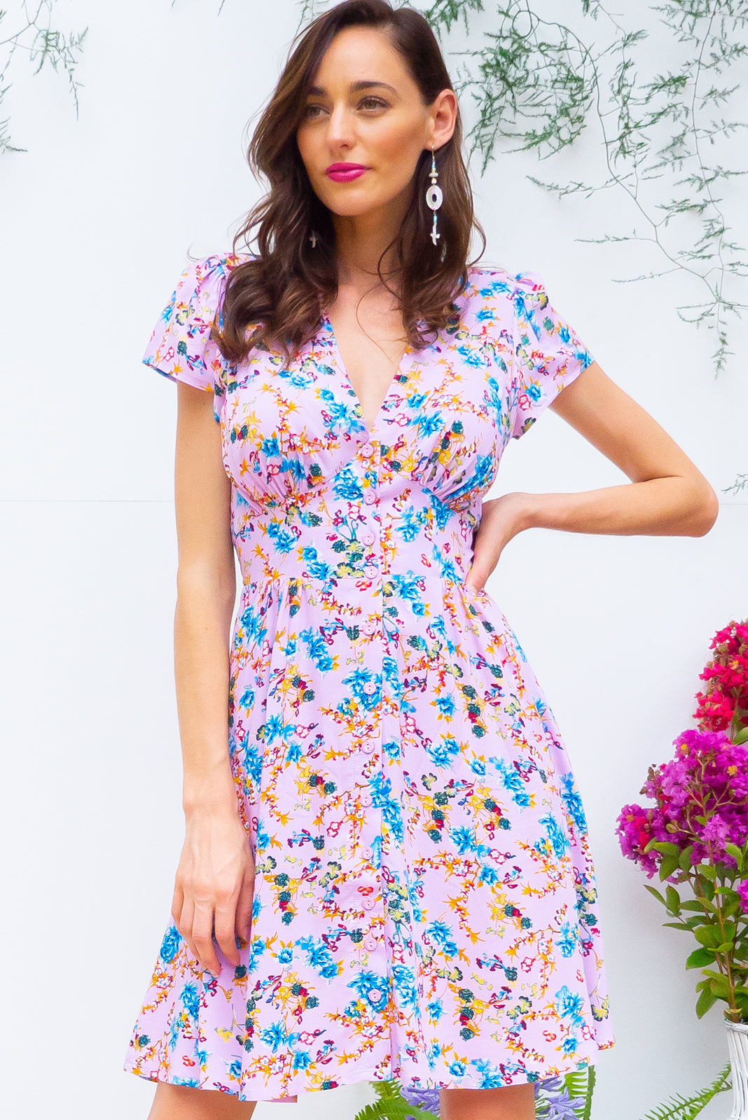 Peggy Portia Mini dress features a vintage inspired fitted basque waist and elasticated waist with a cap sleeve, deep v neck and a functional button front the fabric is a soft woven rayon in a fresh pink purple floral print