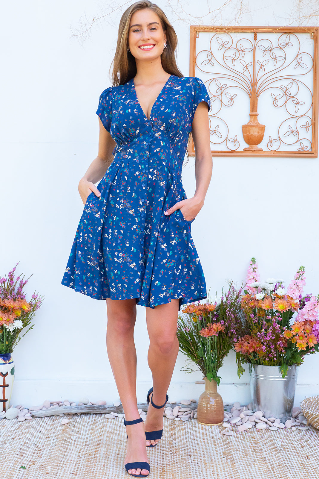Peggy Venetians Blues Mini dress features a vintage inspired fitted basque waist and elasticated waist with a cap sleeve, deep v neck and a functional button front the fabric is a soft woven rayon in a pastel navy and floral print