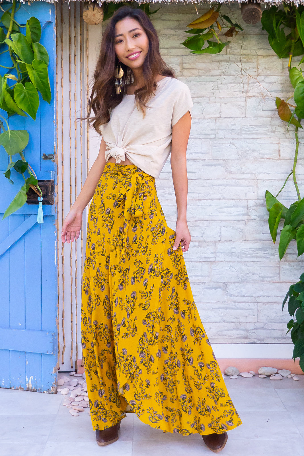 Penny Lane Gold Sprig Maxi Wrap Skirt with an adjustable wraparound waist and waterfall hemline in a soft woven crinkle textured rayon with a bright rich gold floral print