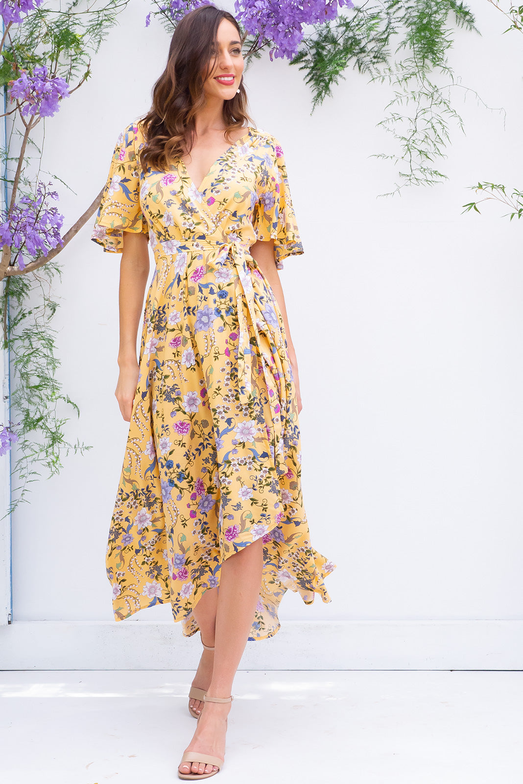 Penny Melody Yellow Maxi Wrap Dress features a soft buttercup yellow base with a delicate floral bohemian print on a soft woven rayon and has a petal sleeve and wrap around shape