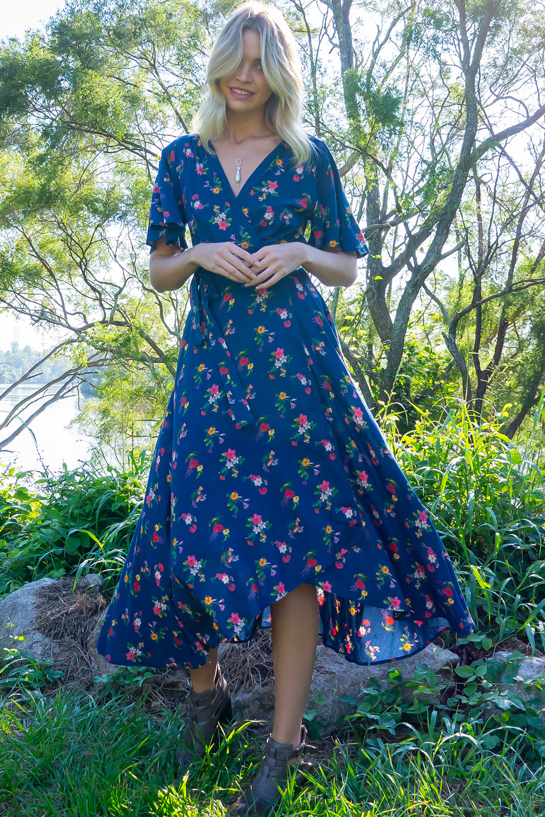 The Petal Blue Elderberry Maxi Wrap Dress features plunging neckline, ties at waist, elasticised waistband at back, floaty petal sleeves, side pockets and 100% rayon in rich navy base with multicoloured floral print.
