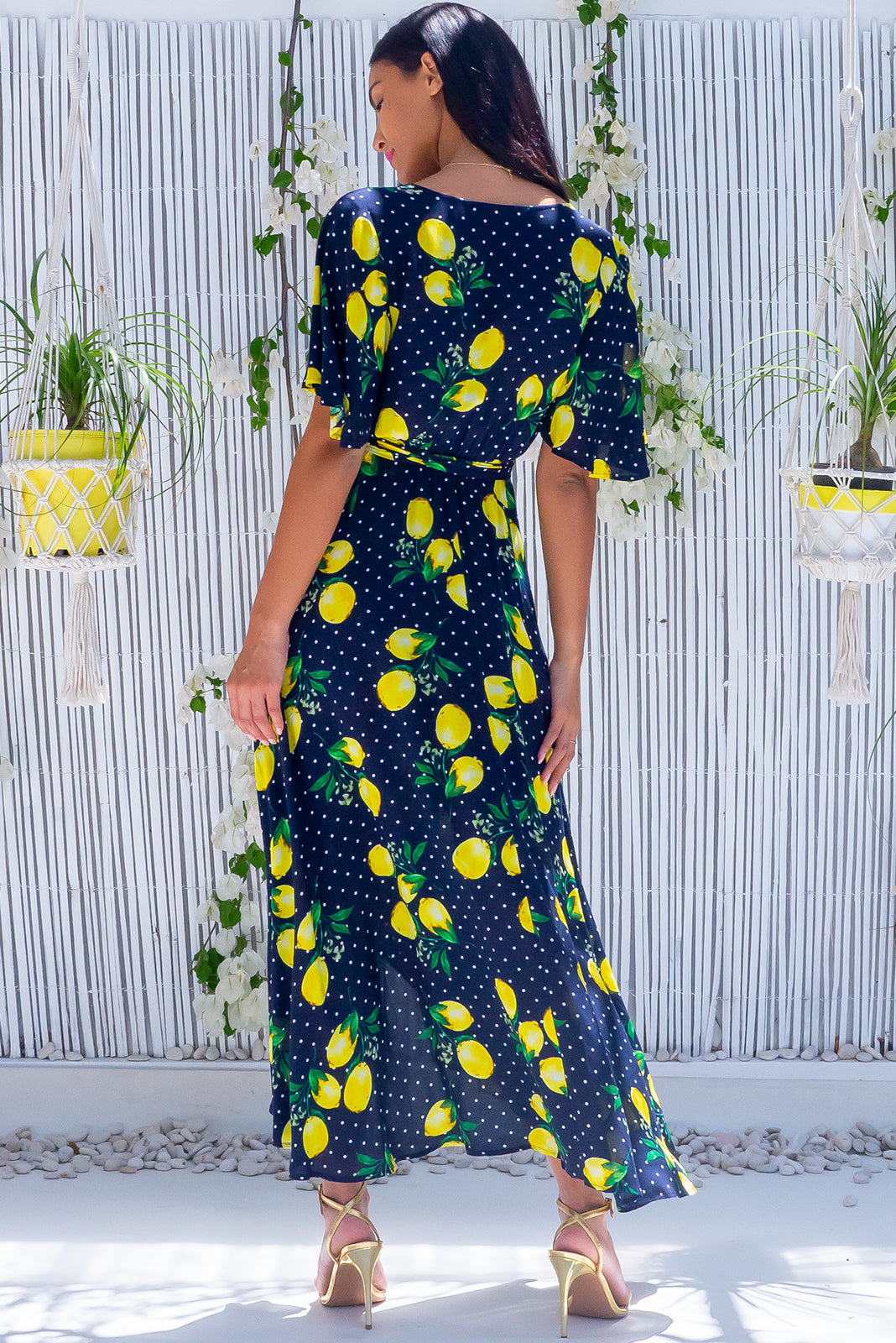 The Petal Limoncello Ink Maxi Wrap Dress features plunging neckline, functional wrap design, elasticised waistband at back, floaty petal sleeves, side pockets and 100% rayon in ink base with bold lemon print.
