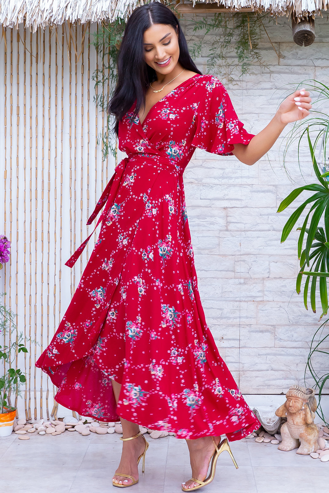 The Petal Red Pansy Maxi Wrap Dress features plunging neckline, midi length at front, maxi length at back, ties at waist., easticised waistband at back, floaty petal sleeves, side pockets and 100% rayon in bold red base with sweet floral print.