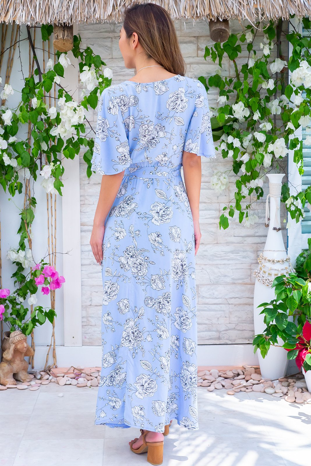 Petal Arctic Garden Maxi Wrap Dress is a stunning retro style featuring adjustable wrap design, flutter sleeves, elasticated waist band at the back, soft, powder blue fabric with a large white floral pattern in woven 100% Rayon.