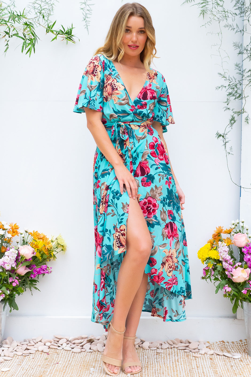 Petal Artists Flowers Maxi Wrap Dress features a flutter sleeve, adjustable wrap around waist and a dipped hemline in a soft woven 100% rayon fabric with a romantic watercolour inspired floral print in a rich turquoise blue