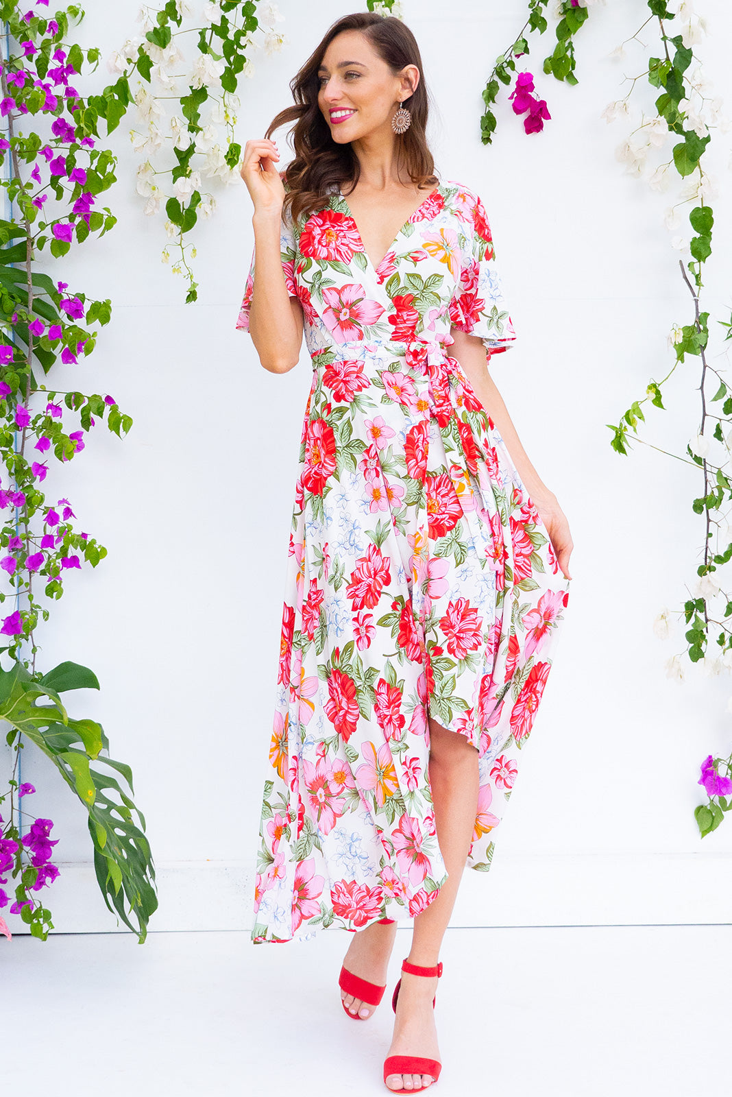 Petal Azalea Pinks Maxi Wrap Dress features a flutter sleeve, adjustable wrap around waist and a dipped hemline in a soft woven 100% rayon fabric with a romantic bohemian floral print in white pink and red