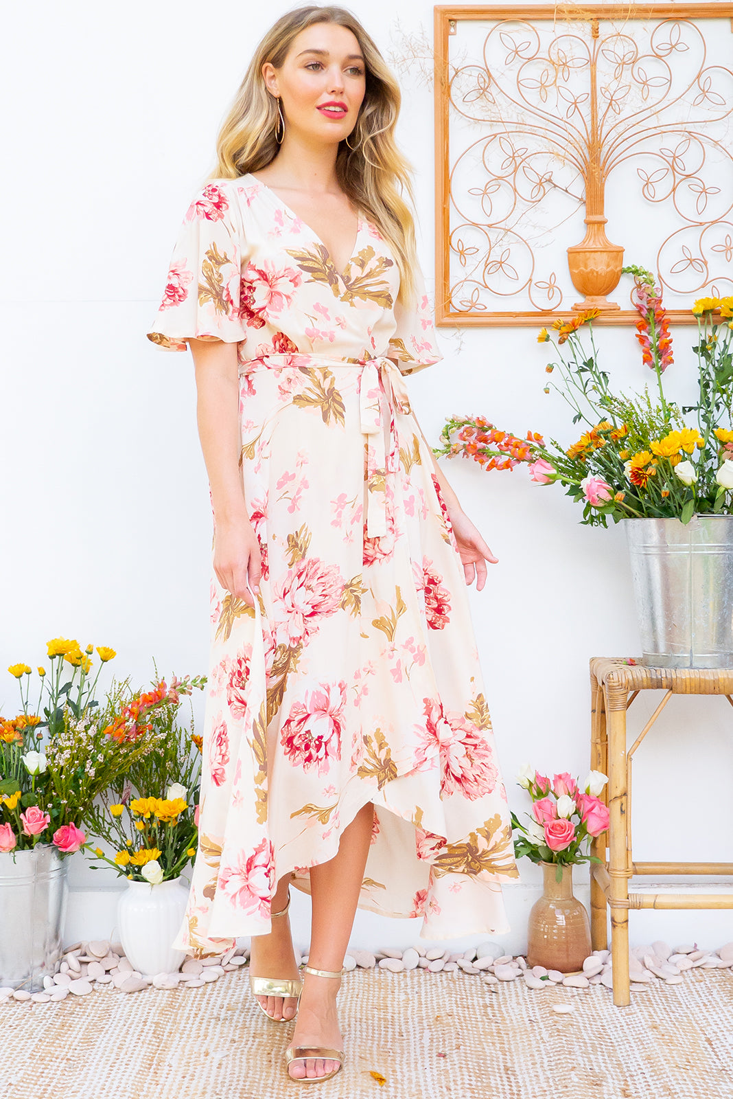 Petal Biscotti Blooms Maxi Wrap Dress features a flutter sleeve, adjustable wrap around waist and a dipped hemline in a soft woven 100% rayon fabric with a romantic bohemian floral print in warm cream and pink tones