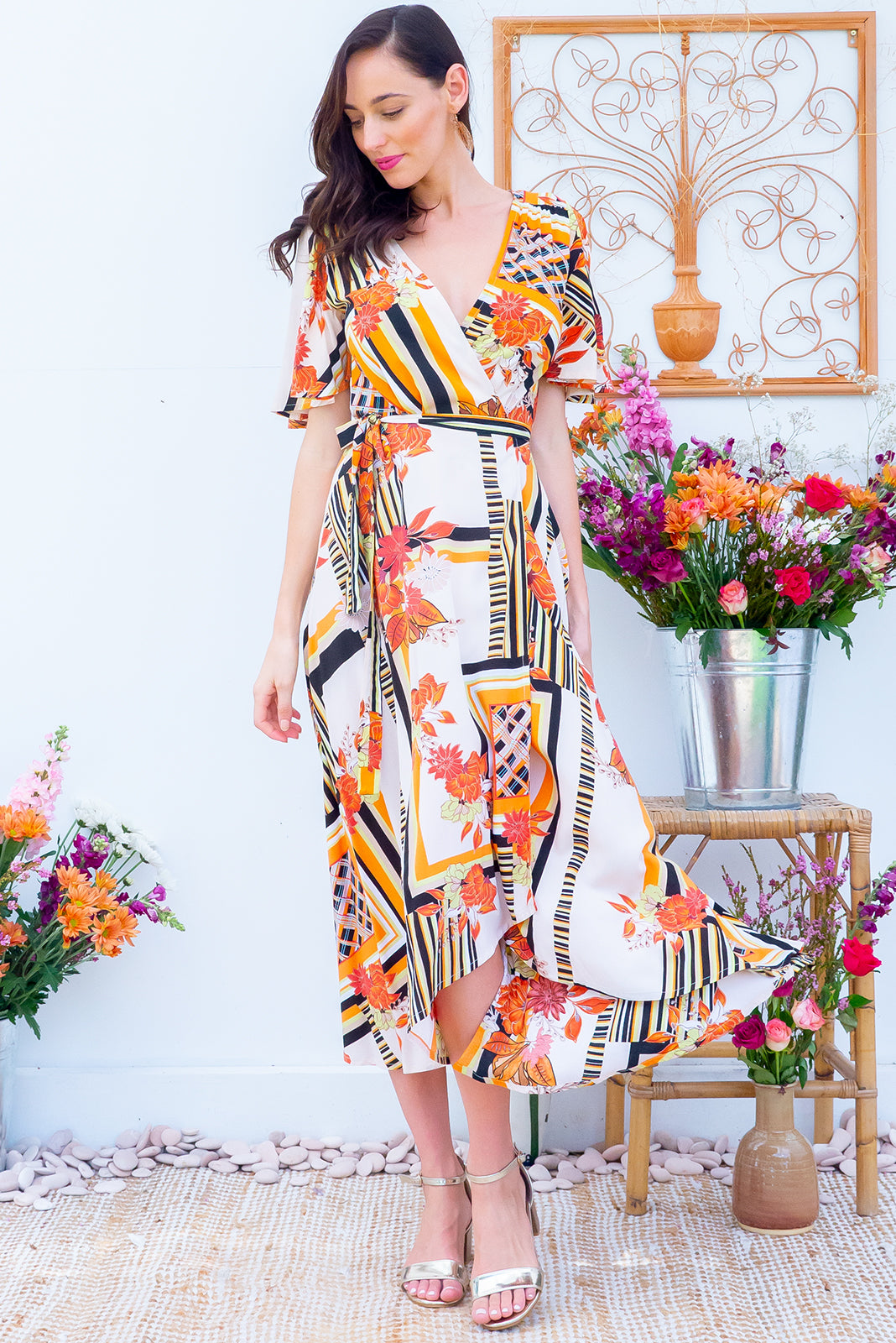 Petal Cider Gold Maxi Wrap Dress features a warm cream base with a black and orange vintage inspired floral bohemian print on a soft woven rayon it features petal sleeves, a wrap around waist and a waterfall hemline