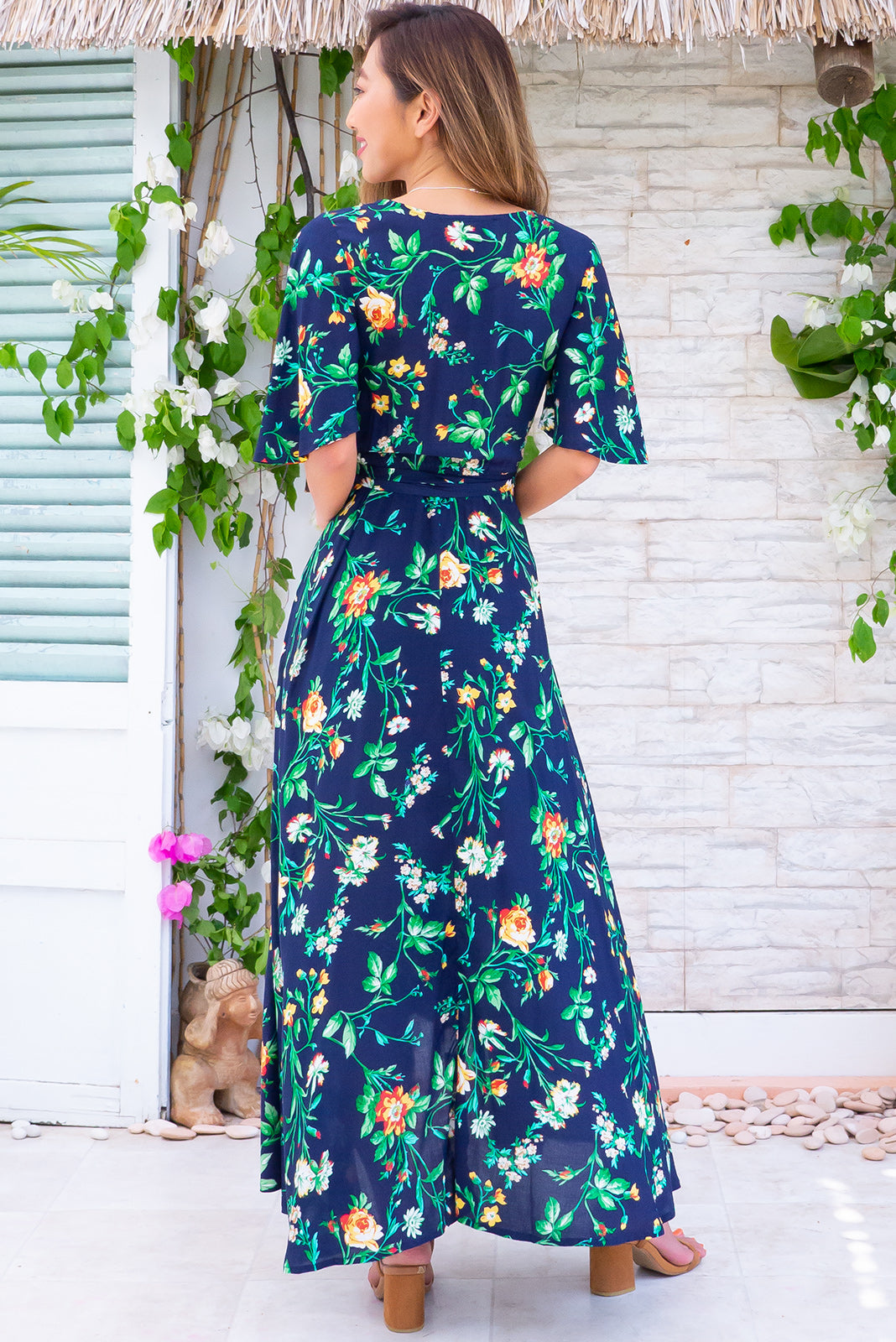 Petal Cotswold Navy Maxi Wrap Dress, ideal events or date night dress features scooped hemline, adjustable wrap design, flutter sleeves, dark navy base, red/yellow vintage rose print in woven 100% rayon.