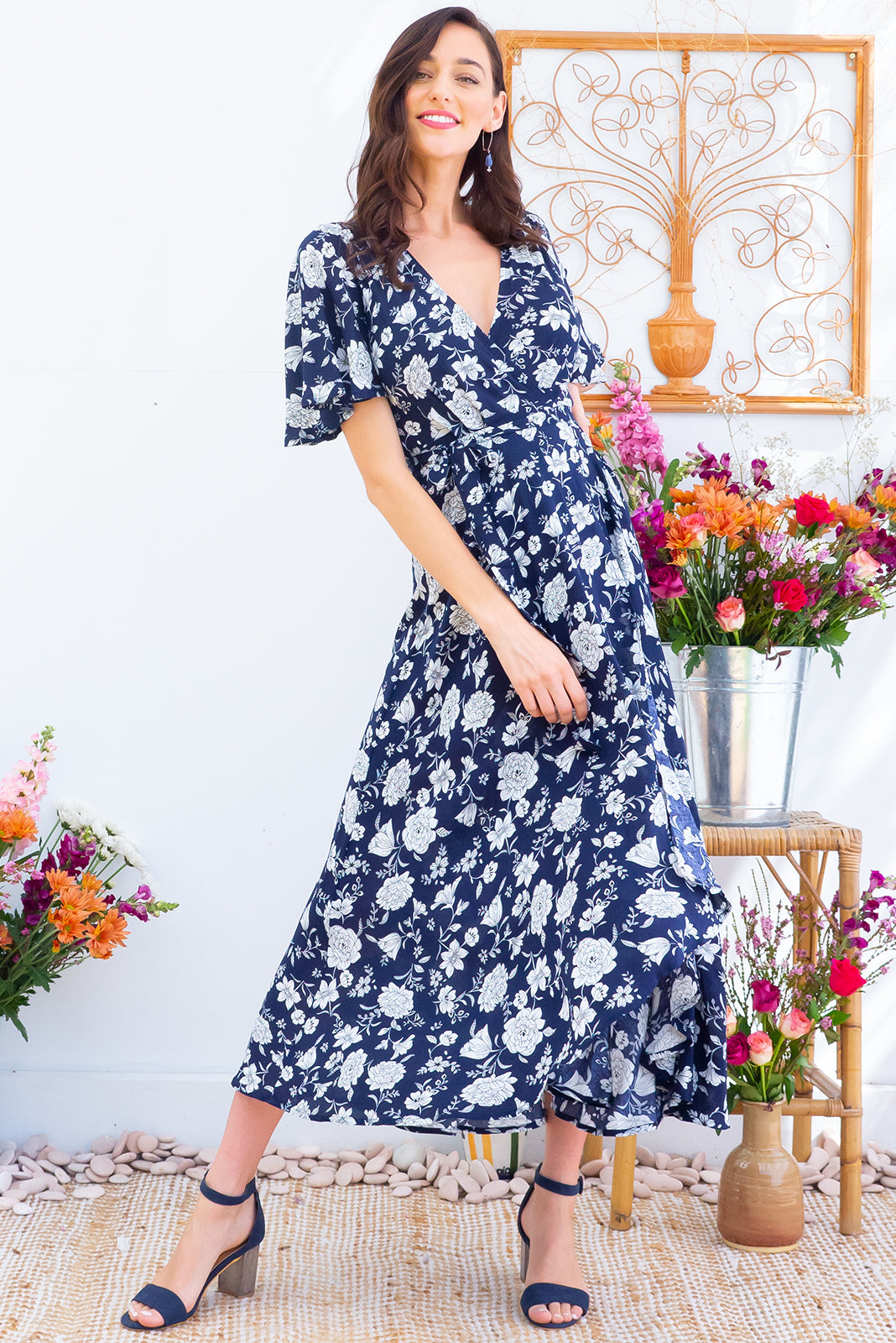 Petal Fortnum Navy Maxi Wrap Dress features a strong navy base with a white floral bohemian print on a soft woven rayon it features petal sleeves, a wrap around waist and a waterfall hemline