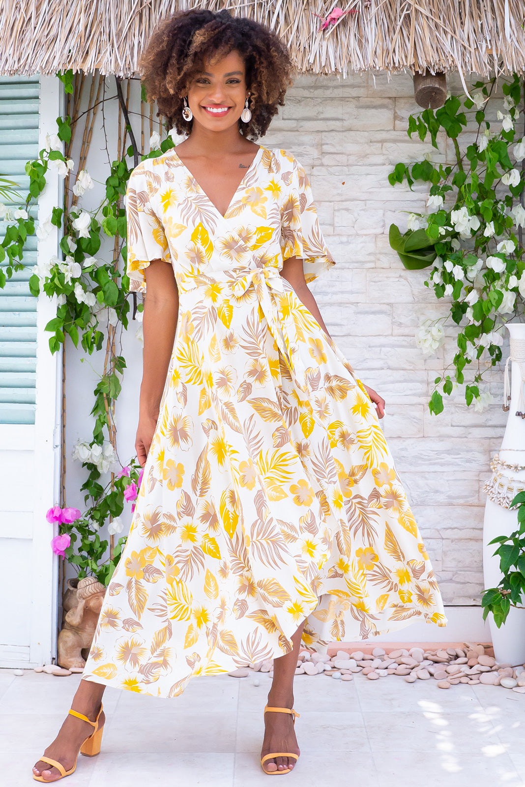 Petal Golden Palms Maxi Wrap Dress, a must-have tropical dress has midi length at front, maxi length at back, elasticised waistband at back, floaty petal sleeves, ream base with yellow gold and taupe floral print in woven 100% rayon.