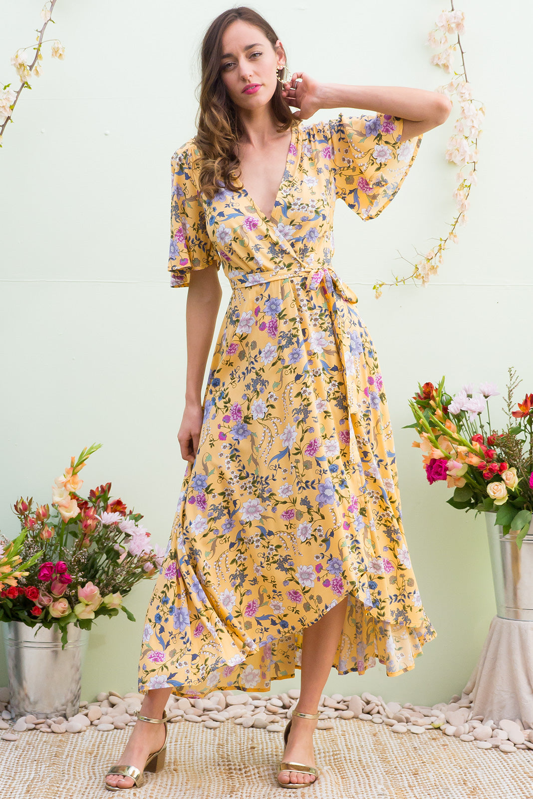 Petal Melody Yellow Maxi Wrap Dress features a soft buttercup yellow base with a delicate floral bohemian print on a soft woven rayon and has a petal sleeve and wrap around shape