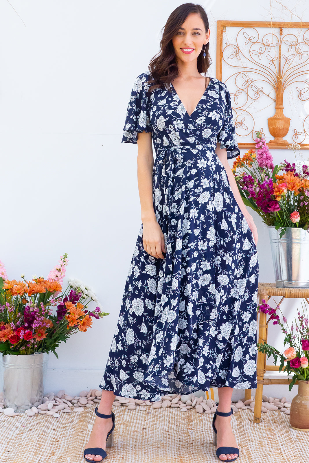 Petal Midnight Roses Maxi Wrap Dress features a strong navy base with a white floral bohemian print on a soft woven rayon it features petal sleeves, a wrap around waist and a waterfall hemline