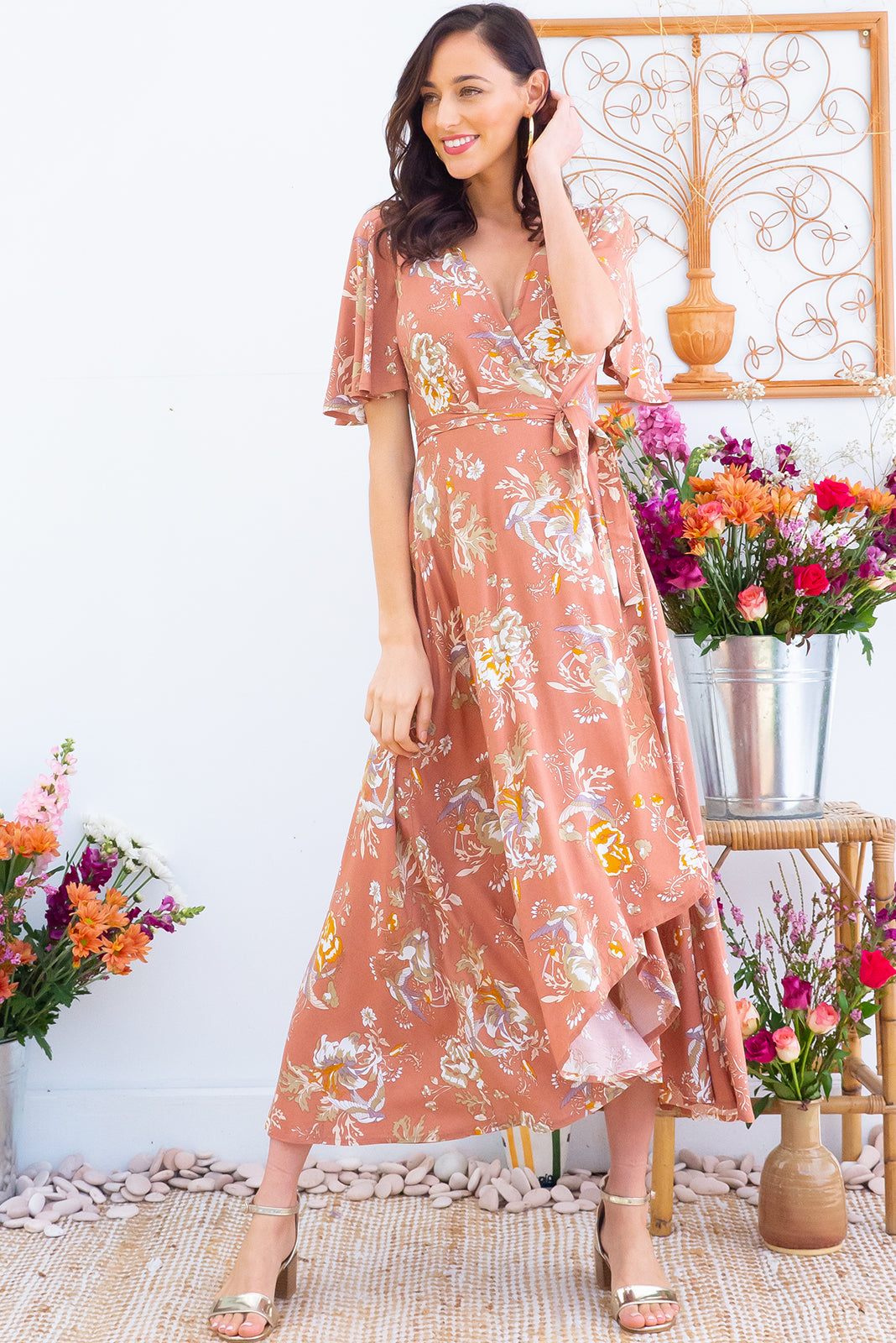 Petal Sepia Sparrow Maxi Wrap Dress features a flutter sleeve, adjustable wrap around waist and a dipped hemline in a soft woven 100% rayon fabric with a romantic bohemian floral and bird print in a soft terracotta tone